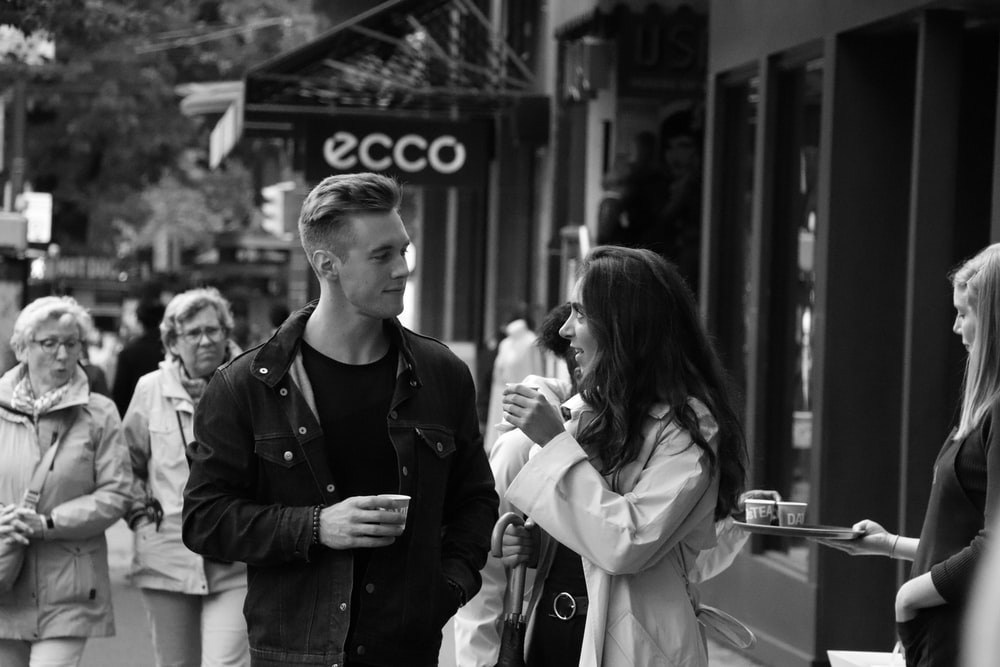 grayscale of woman and man talking each other