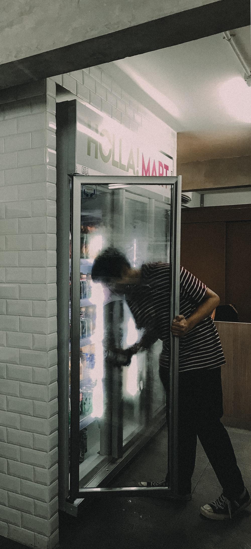 man grabbing drink in fridge