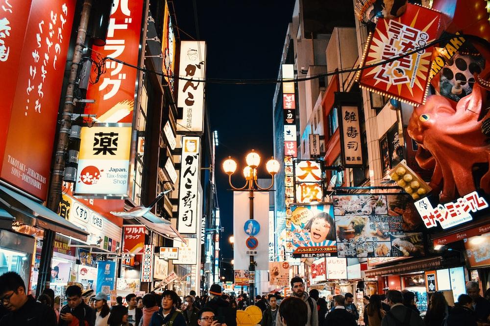 people standing between buildings at night