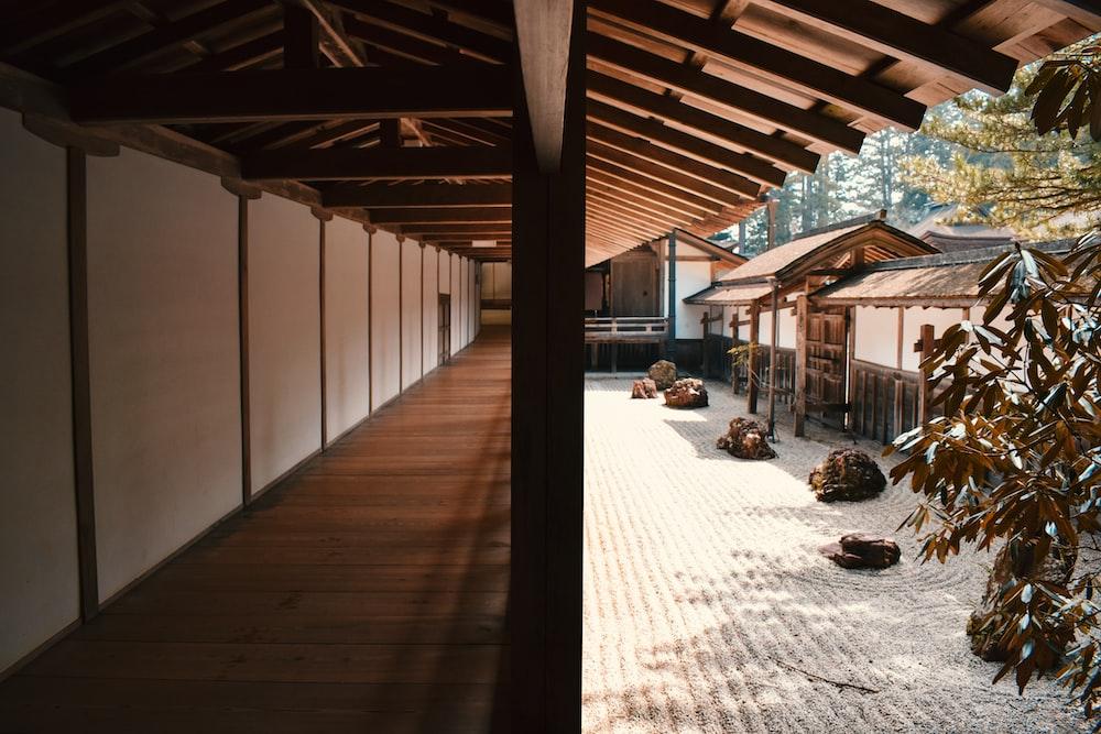 brown wooden flooring beside wall