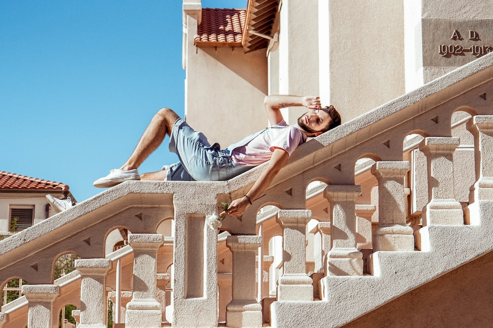 man lying on gray staircase