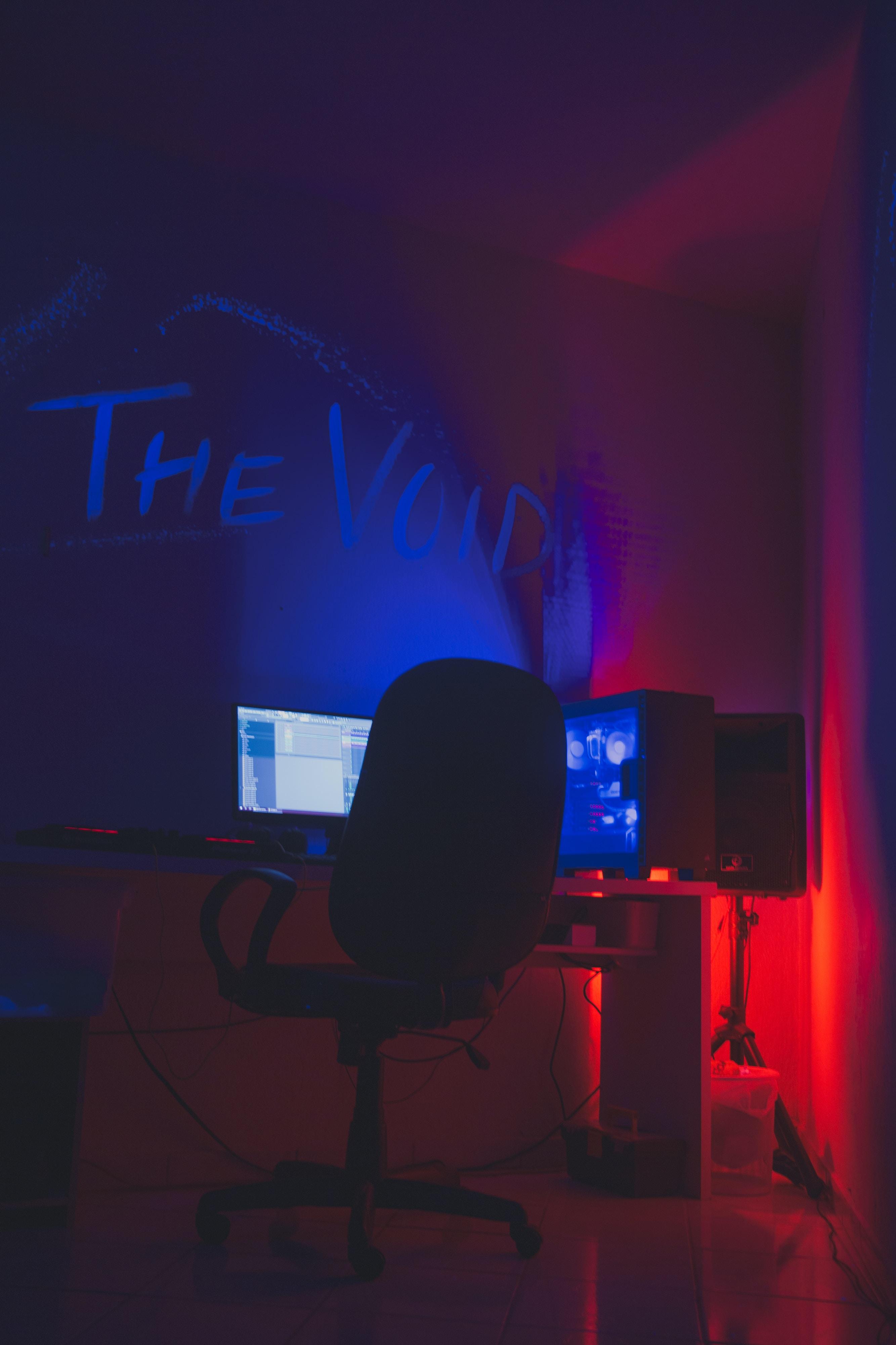 rolling chair beside desktop set inside room with dimmed light