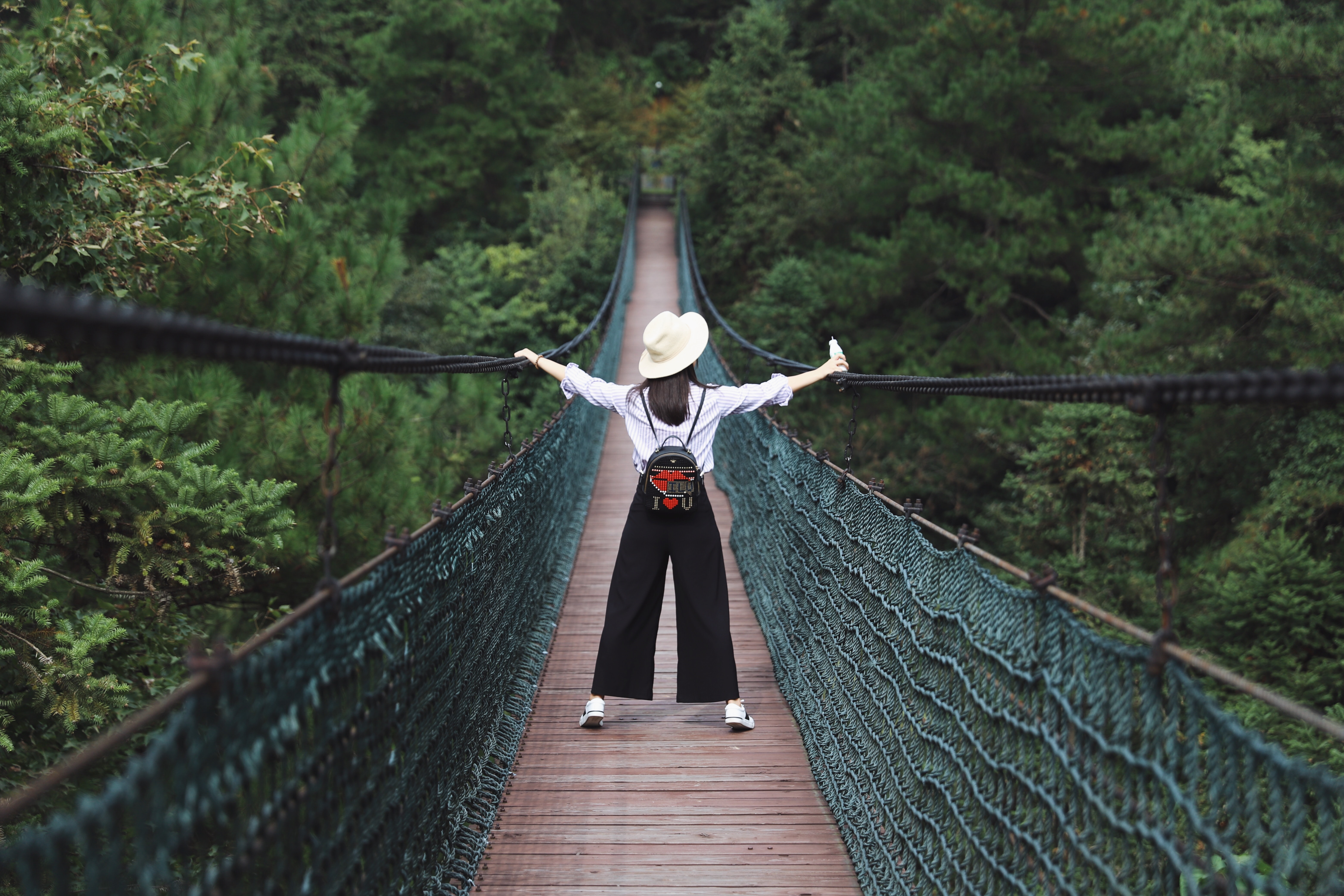 woman standing on hanging bridge surrounded by trees
