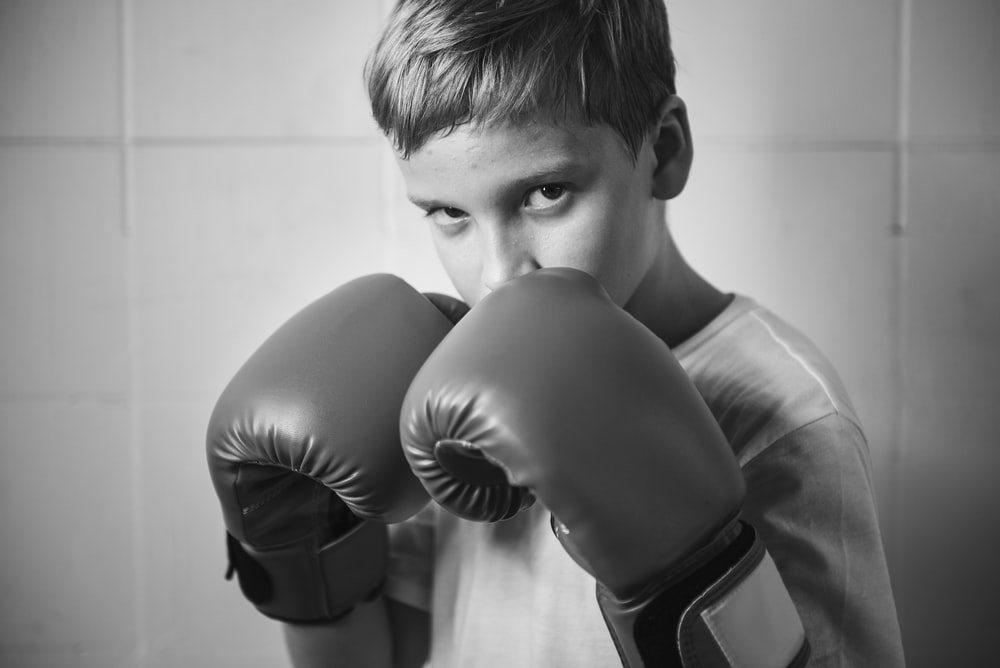 grayscale photo of boy wearing boxing gloves