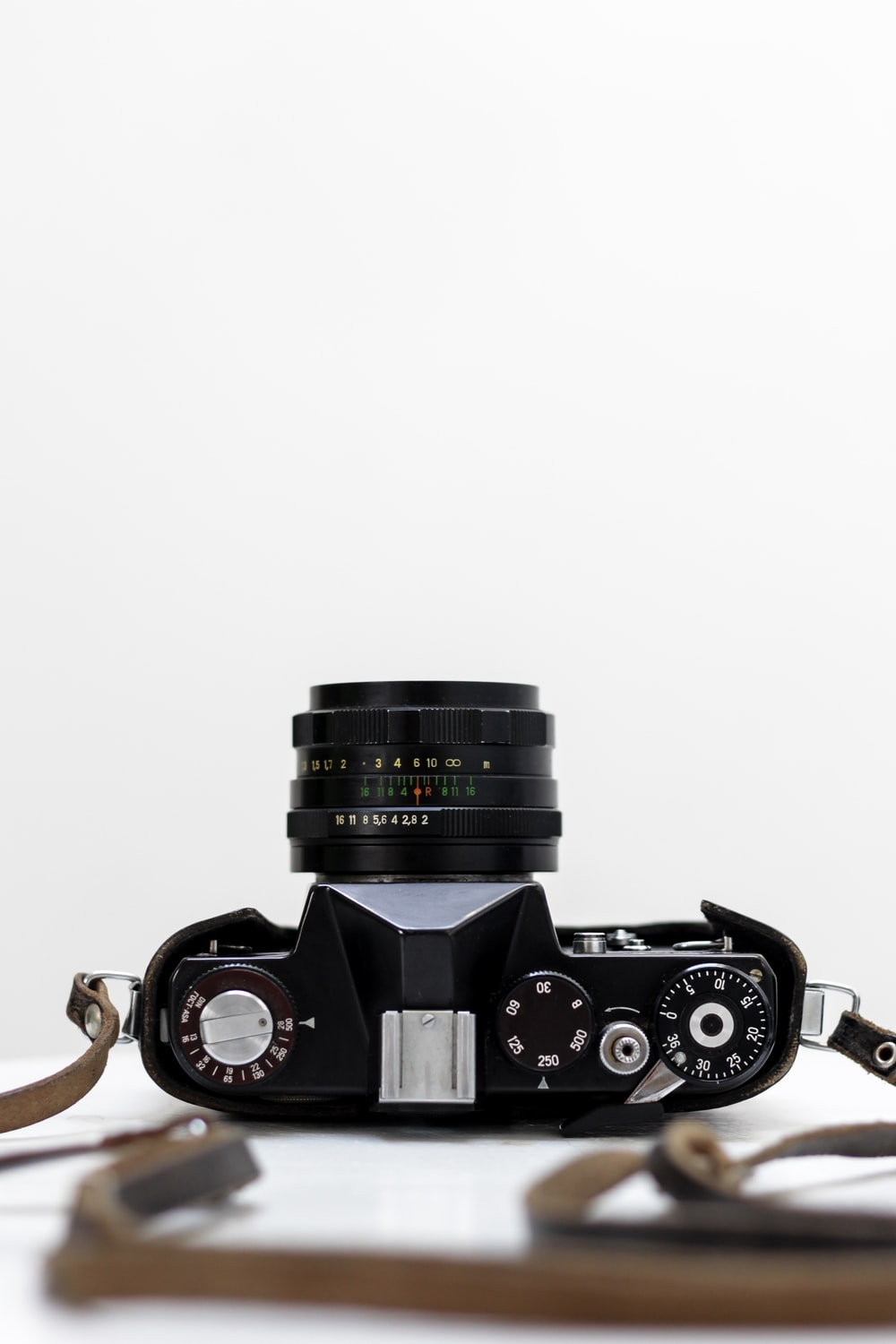 black and grey DSLR camera with white background