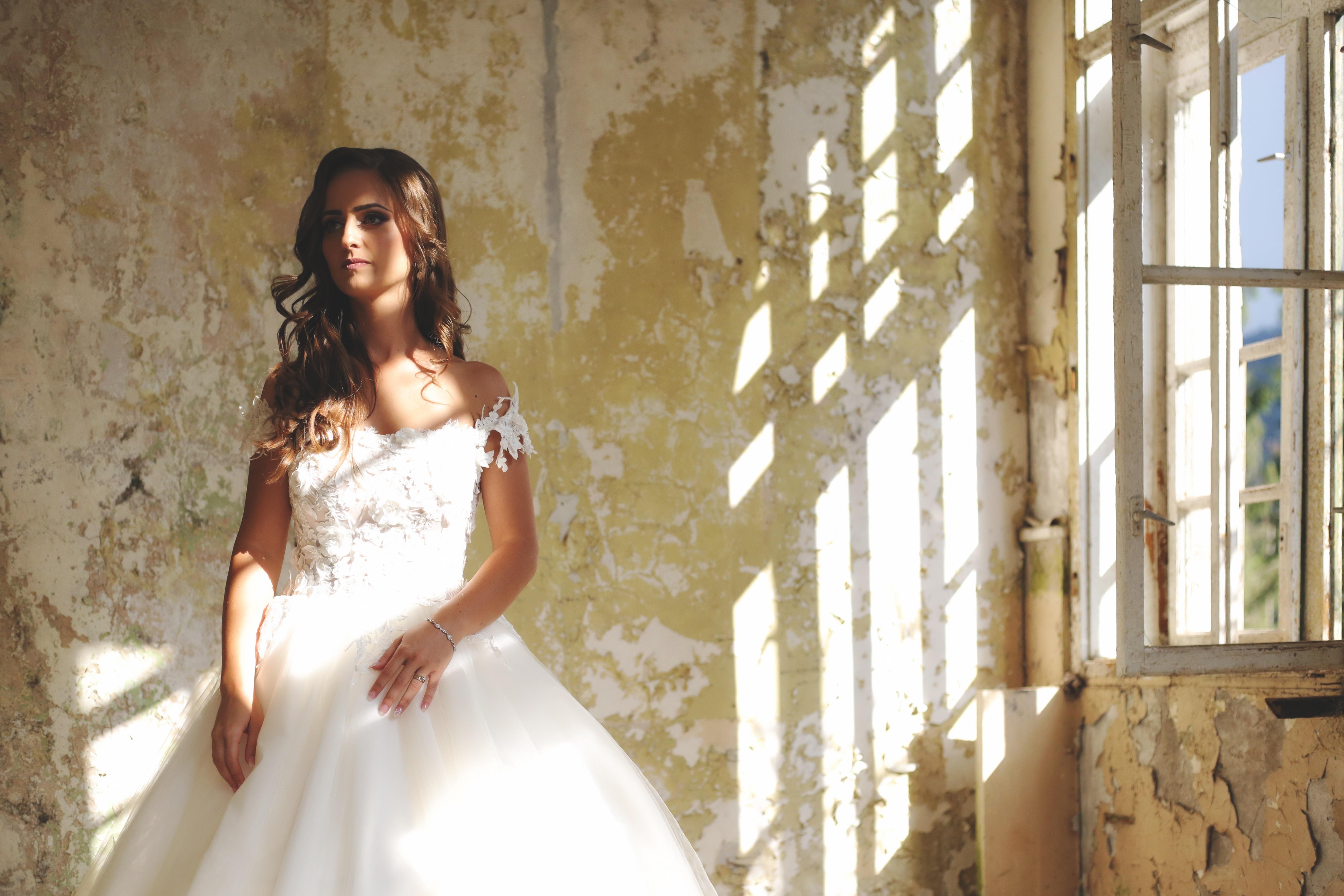woman in bridal gown standing near window