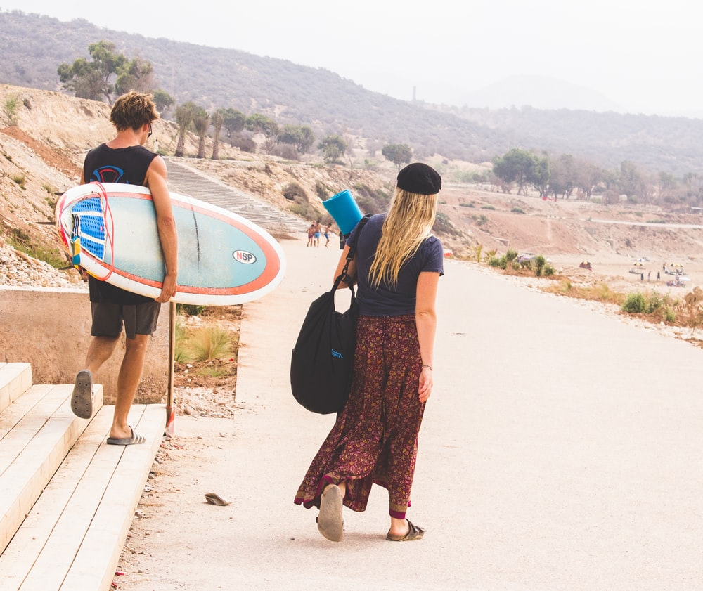 man holding surfboard while walking with woman