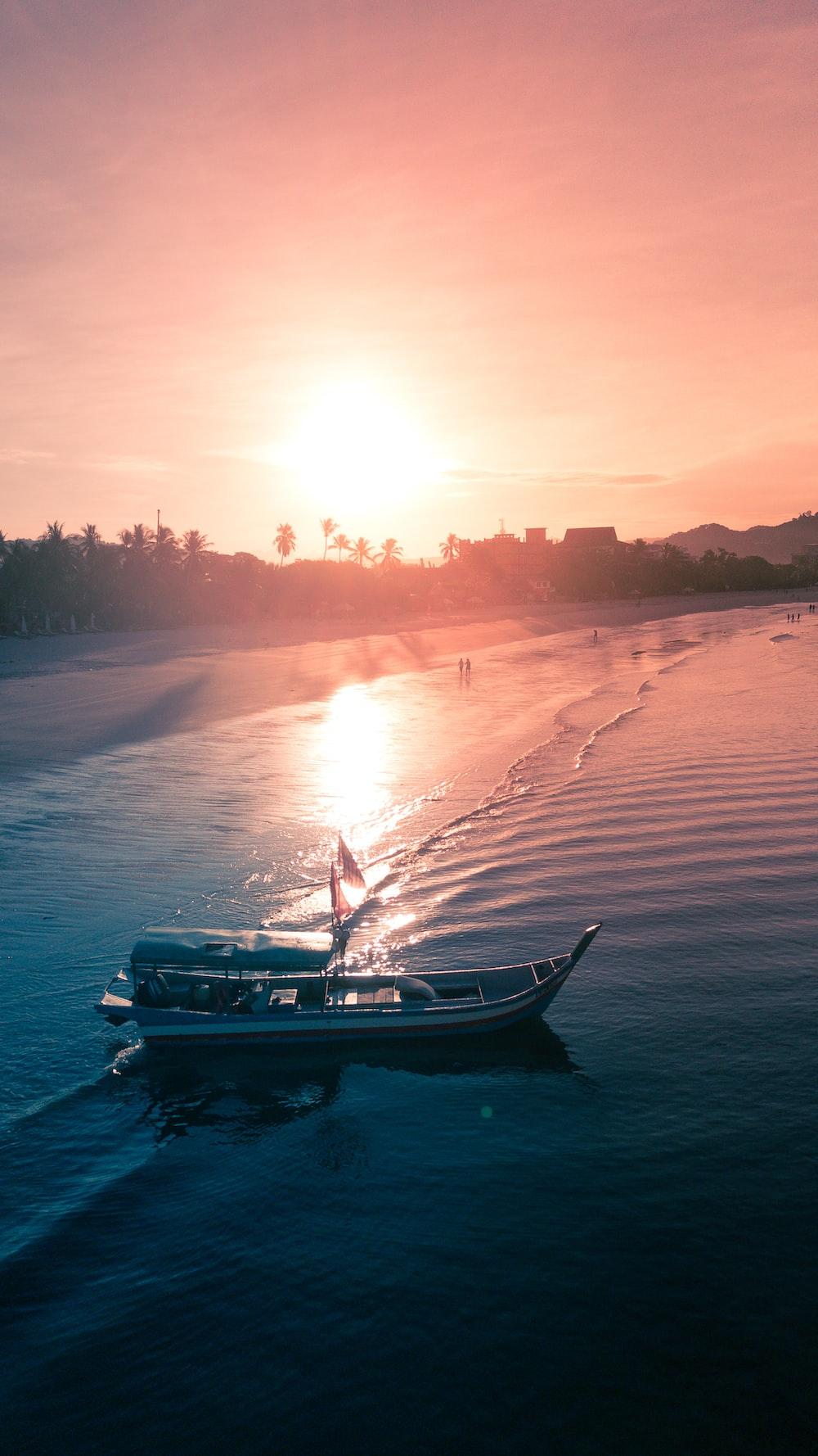 white boat on seashore during sunset time
