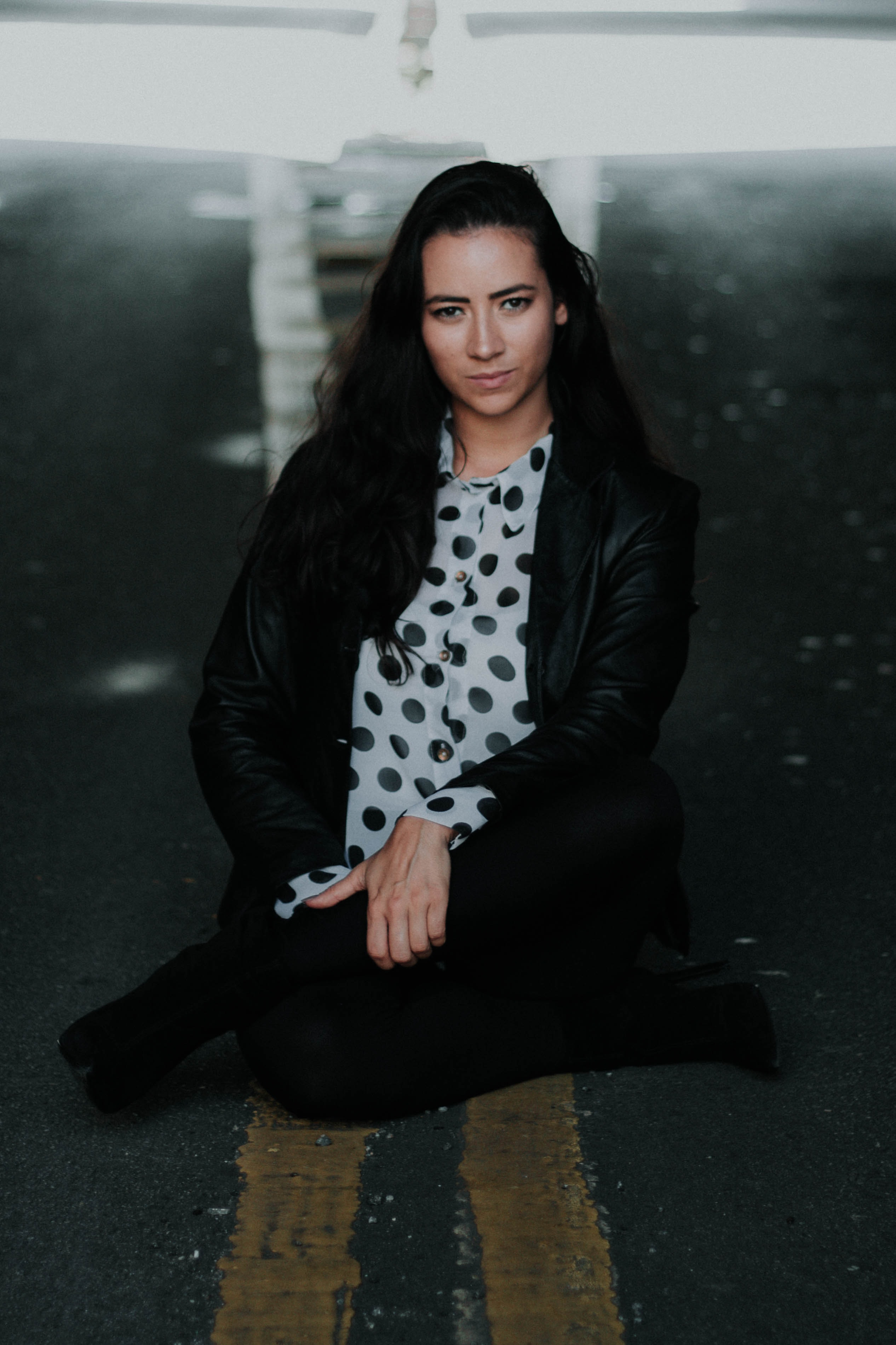 woman in black leather jacket sitting in the middle of the road