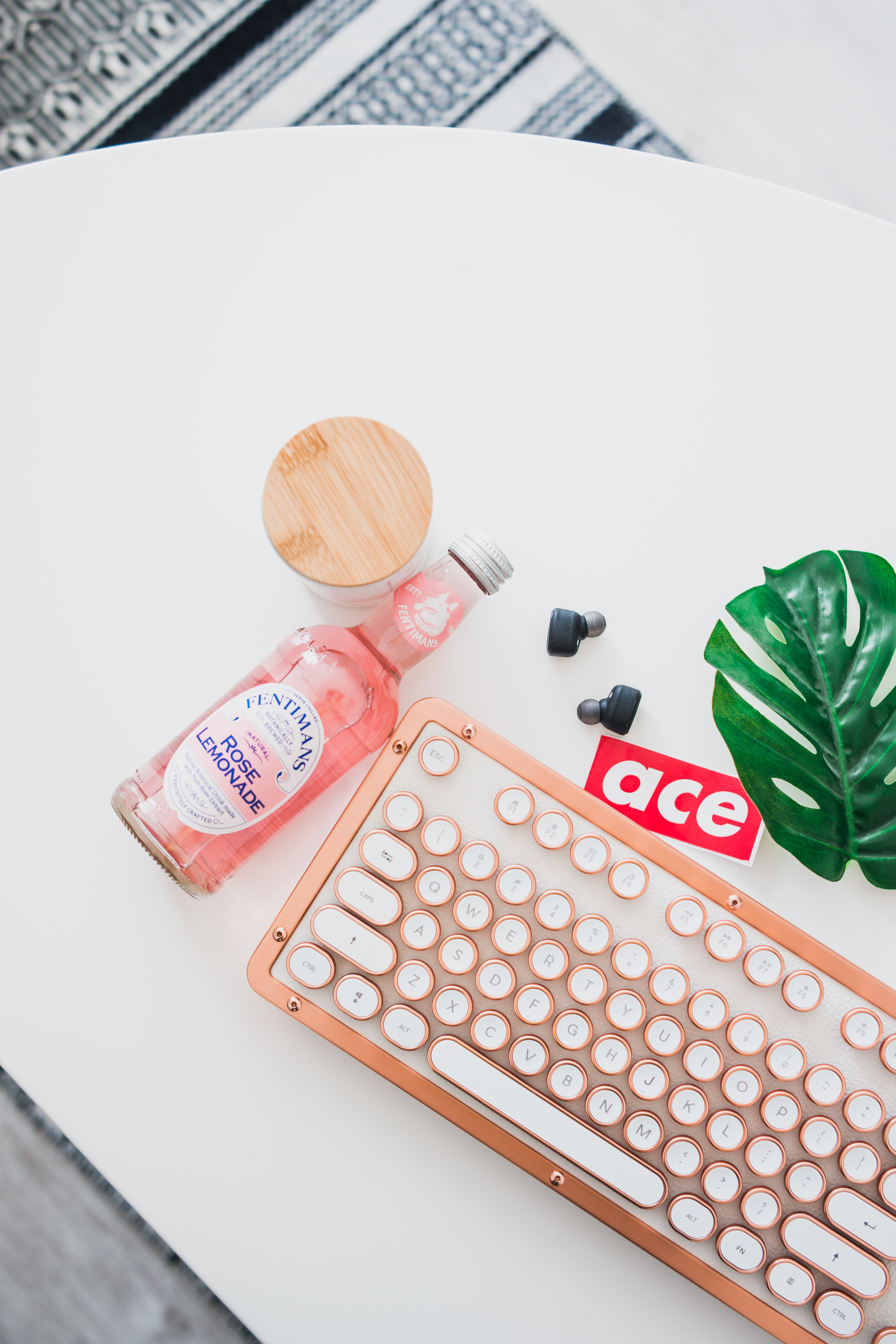 close-up photo of white and brown keyboard and pink bottle on white table