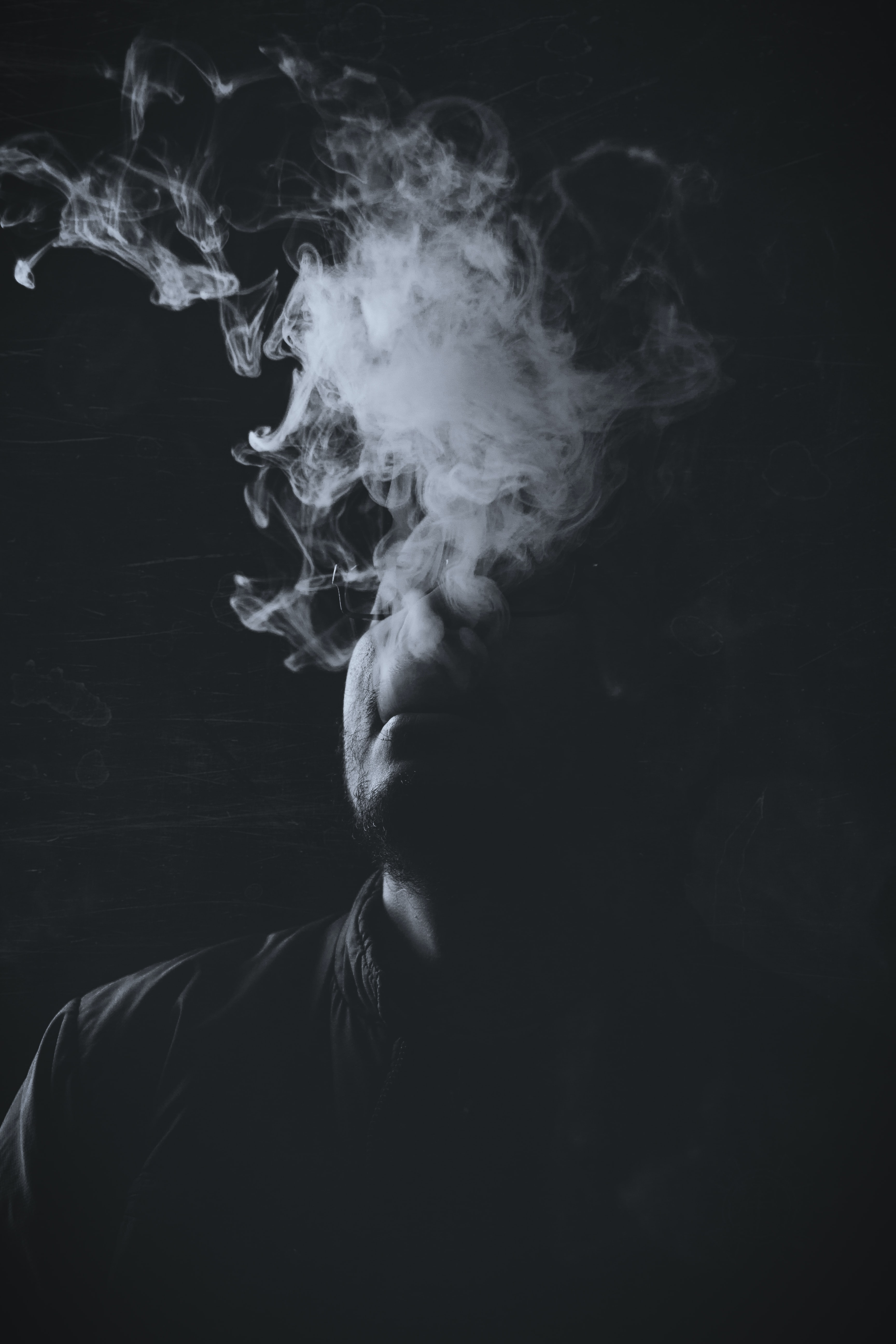 grayscale photograph of man with smoke
