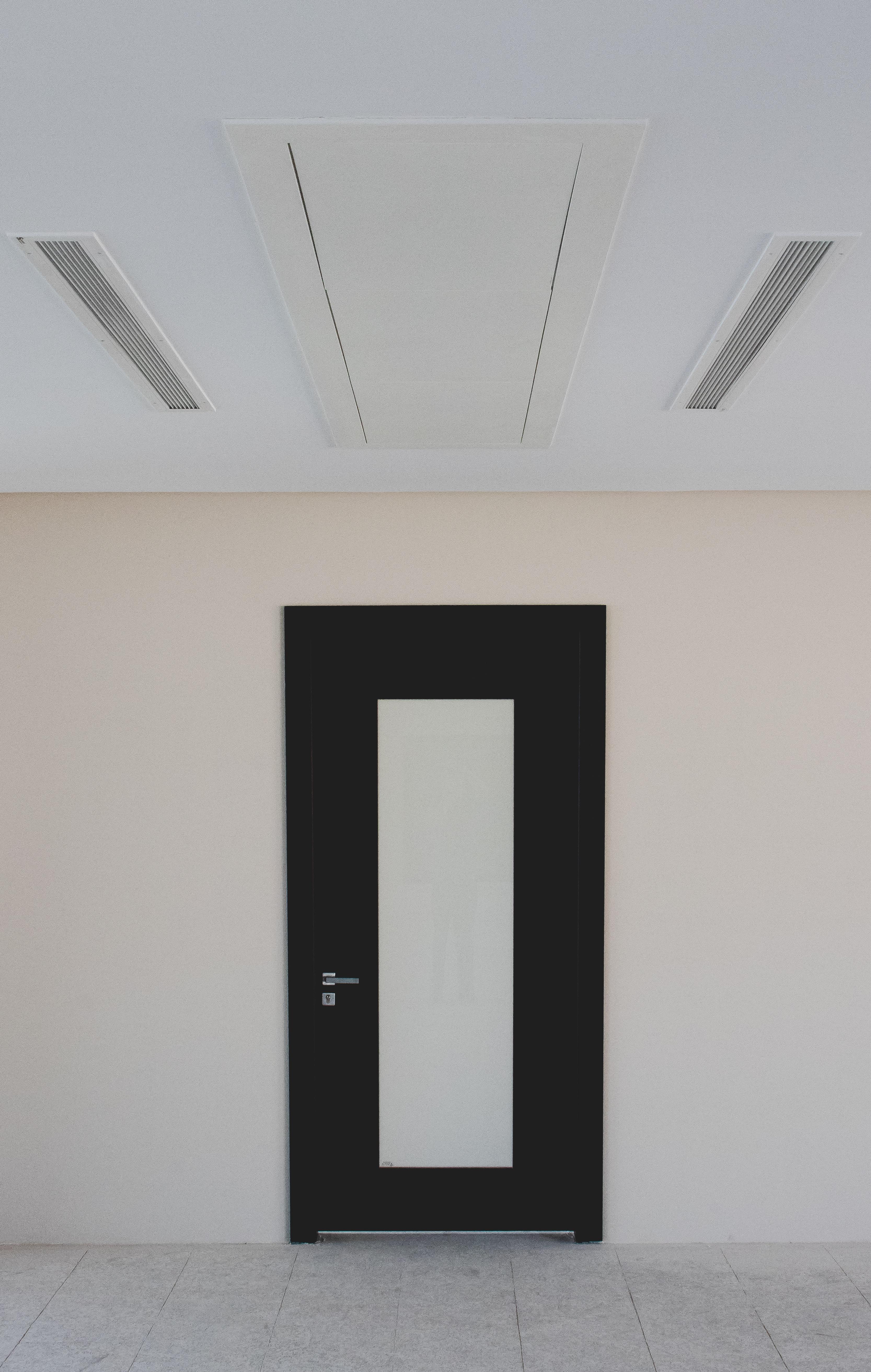 closed black and beige door on beige wall