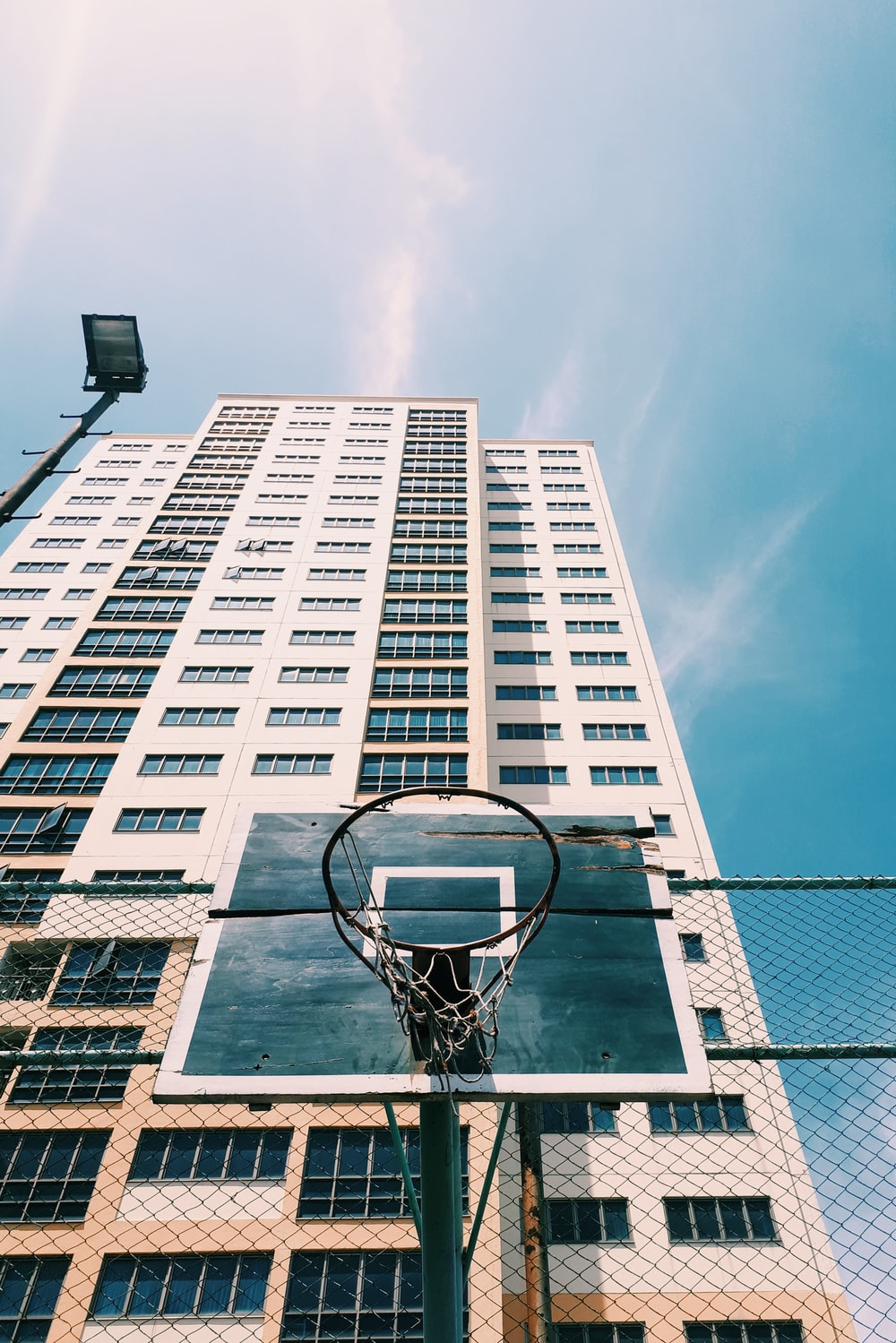 low angle-photography of black and white basketball hoop behind high-rise building during daytime