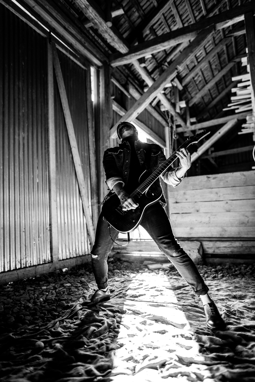 man playing electric guitar beside wall