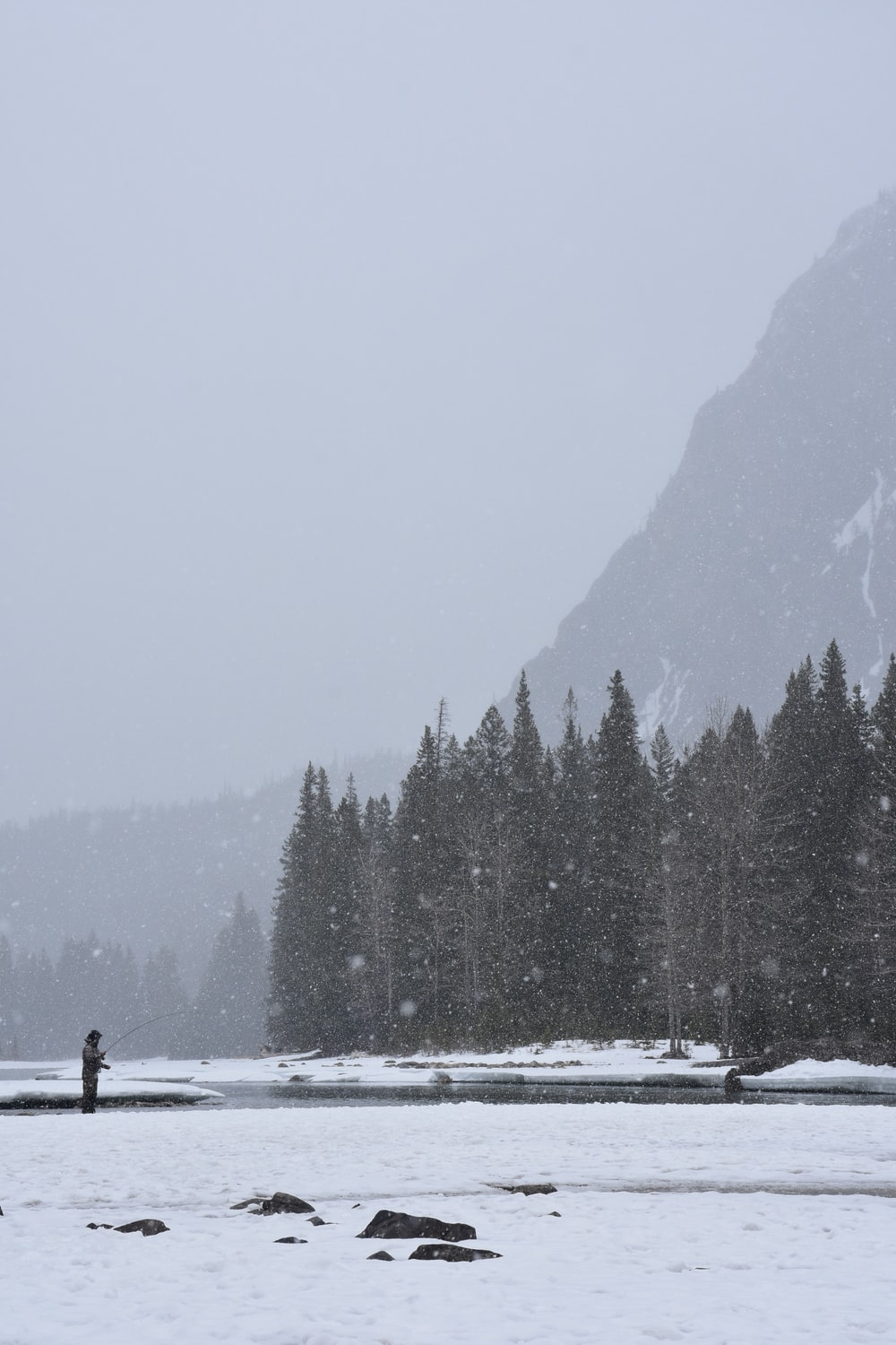 person fishing near body of water during snow