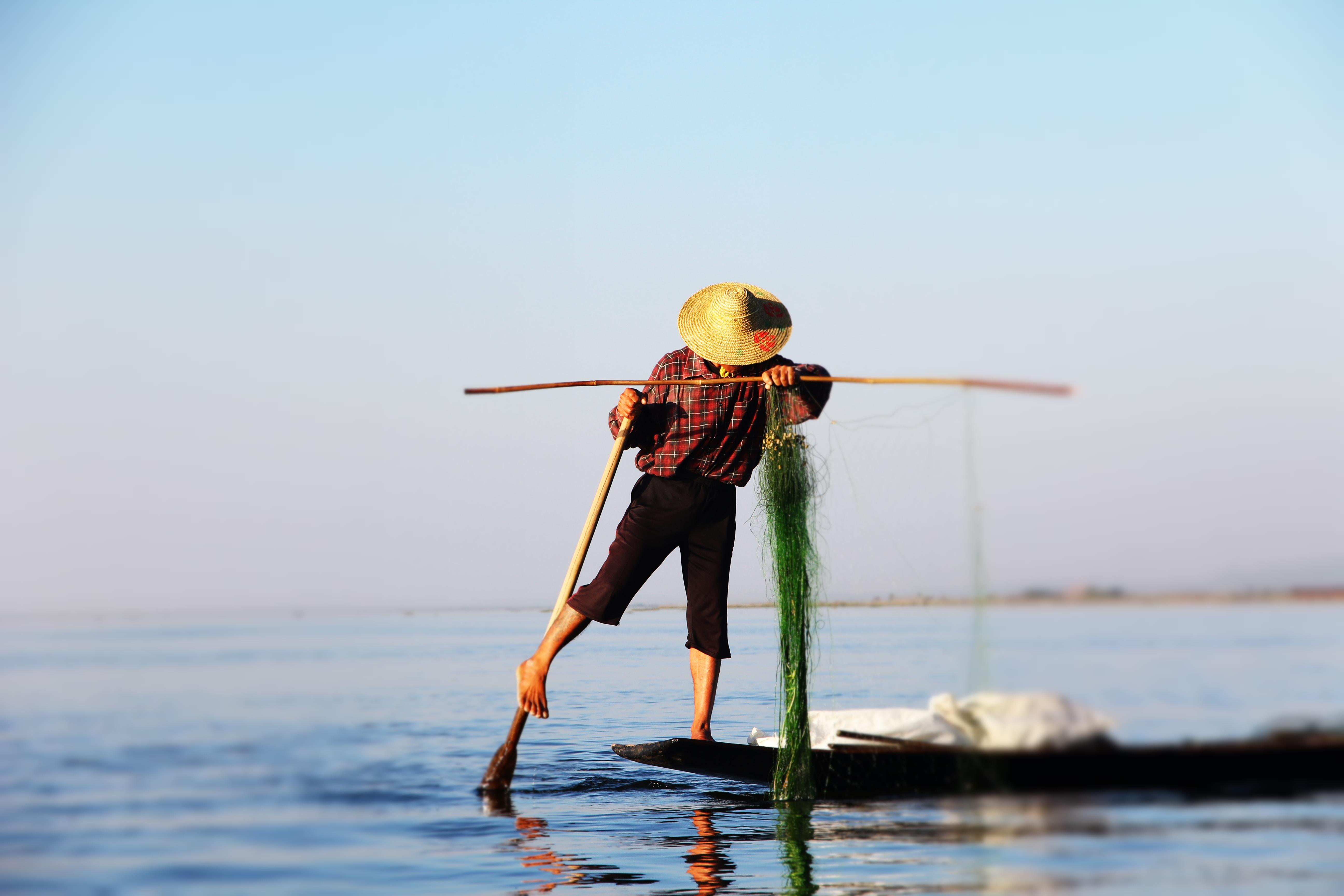 man on boat holding stick