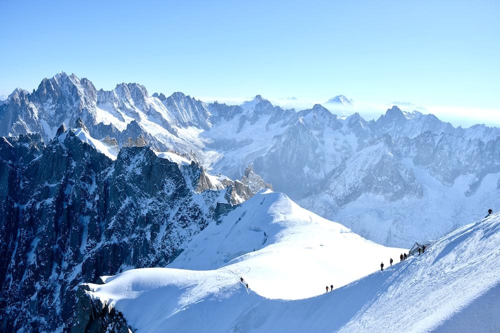 people hiking on snow mountain
