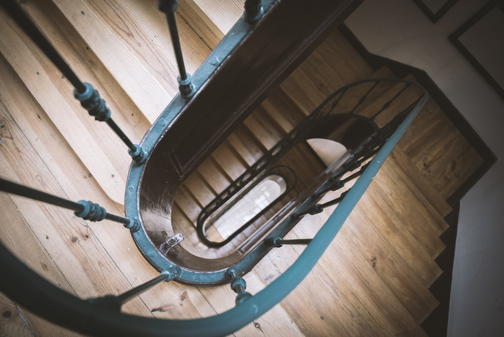brown wooden spiral staircase with blue baluster