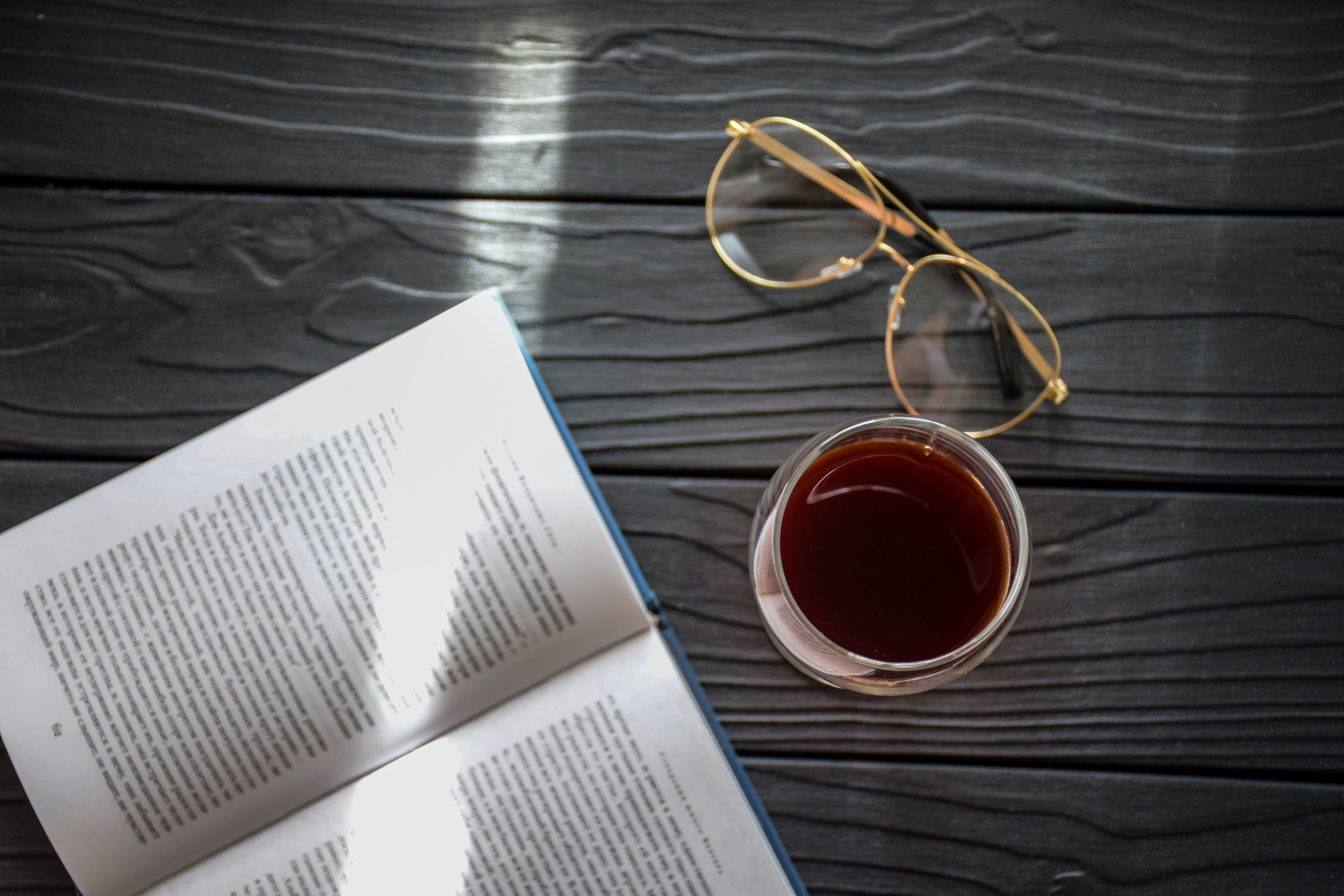 book and eyeglasses beside beverage in glass on gray wood planks