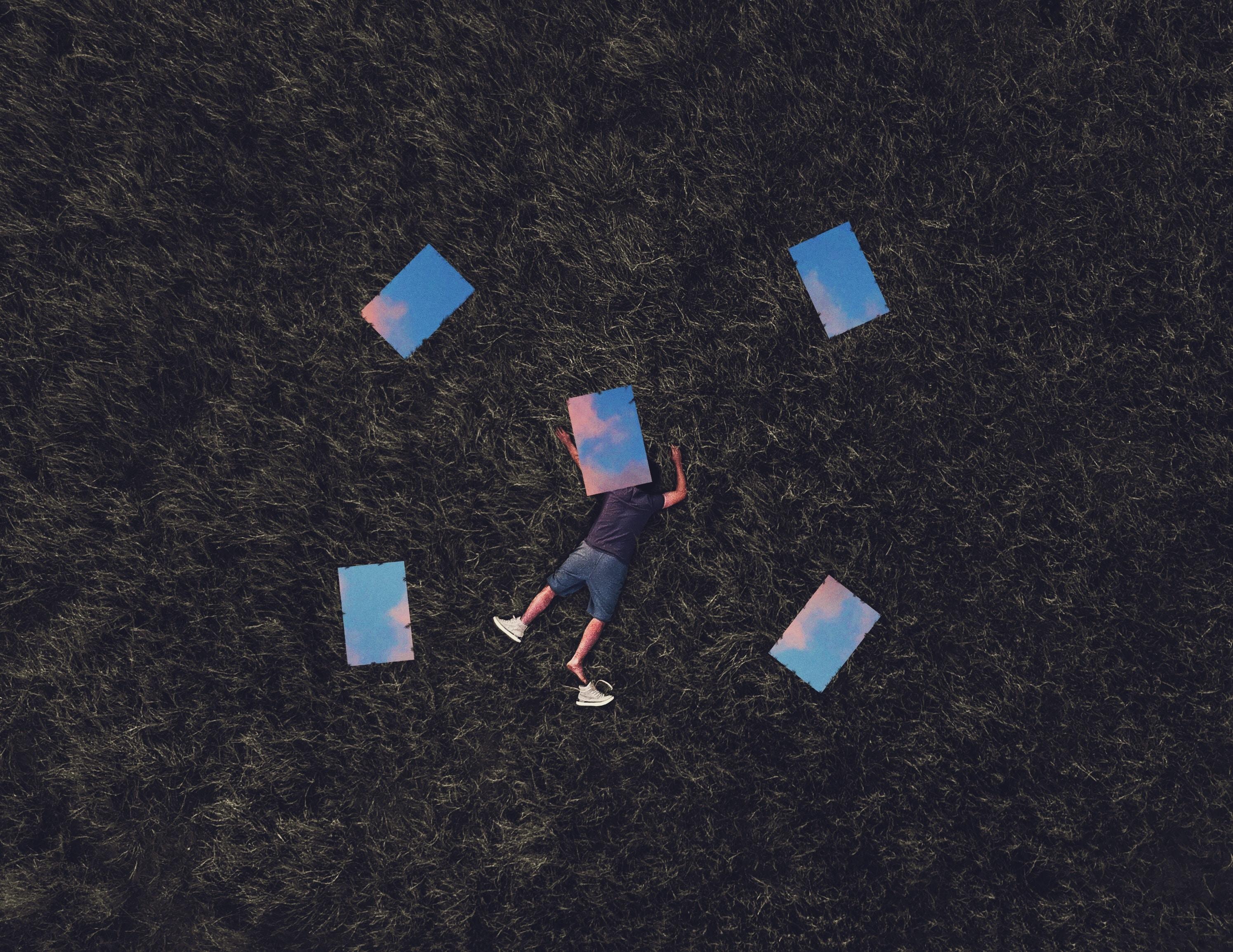 man lying on grass field