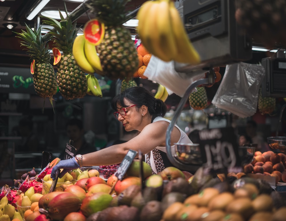 selective focus photography of woman selling fruits