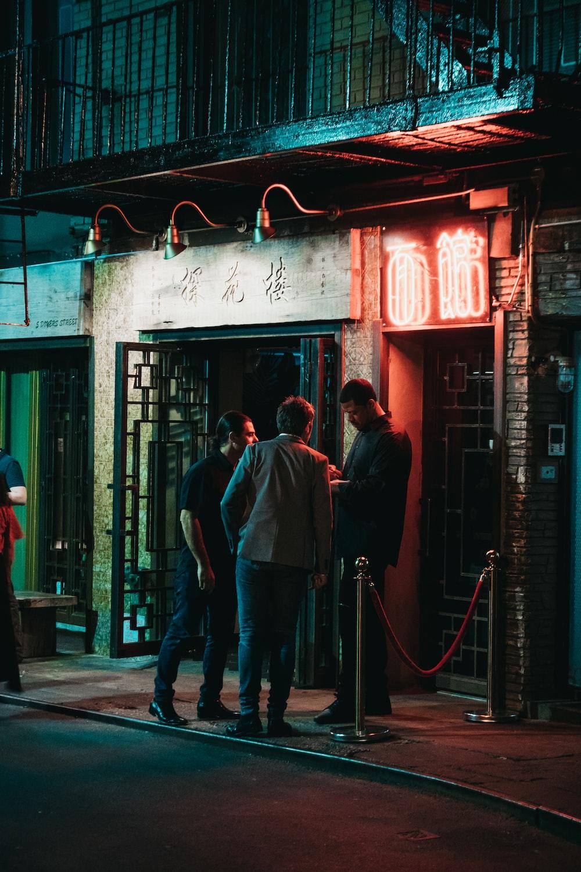 three men standing beside black wooden door