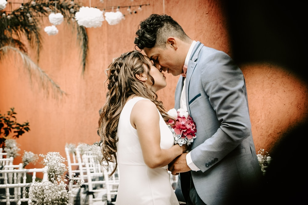 couple beside white fence