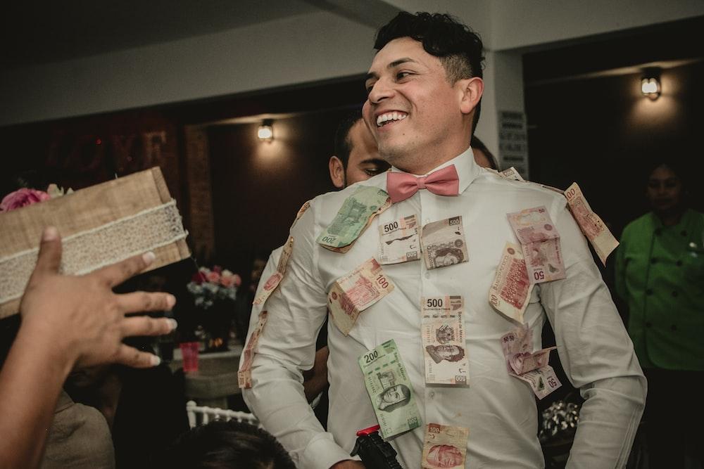 man wearing white formal suit with banknotes hanging