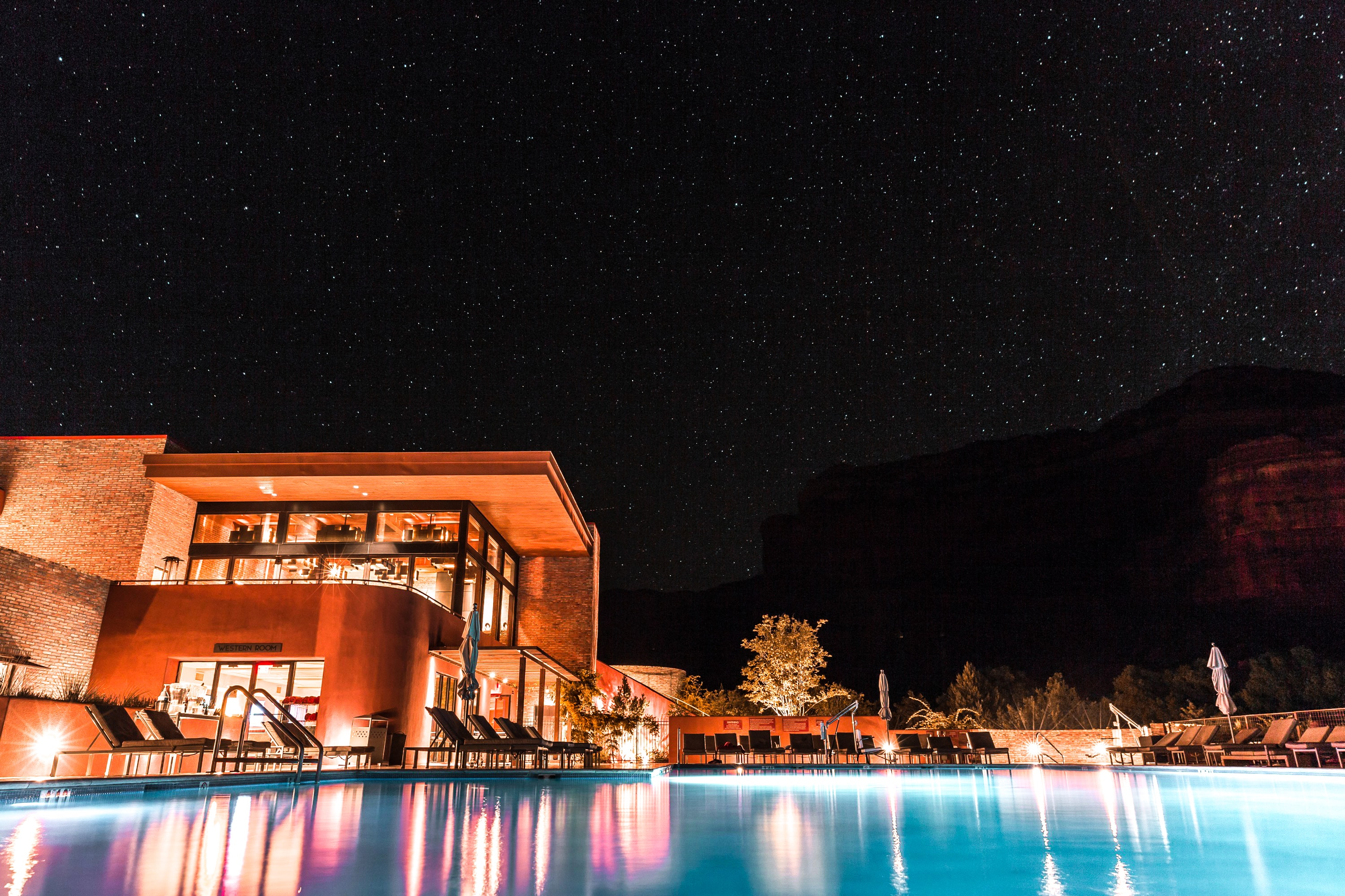 brown and white concrete building beside pool during nighttime
