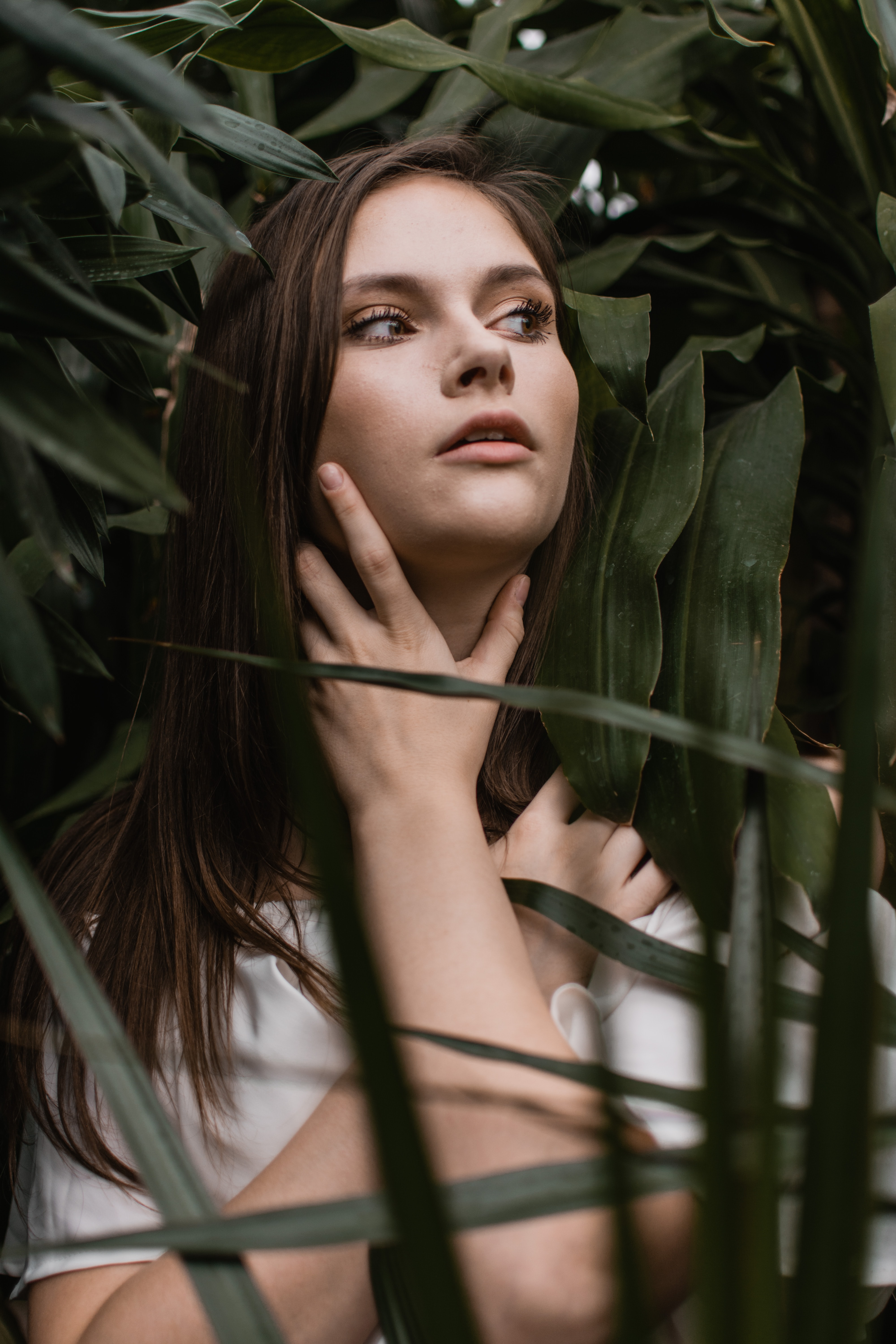 close-up photo of woman holding her neck while standing near plants during daytime