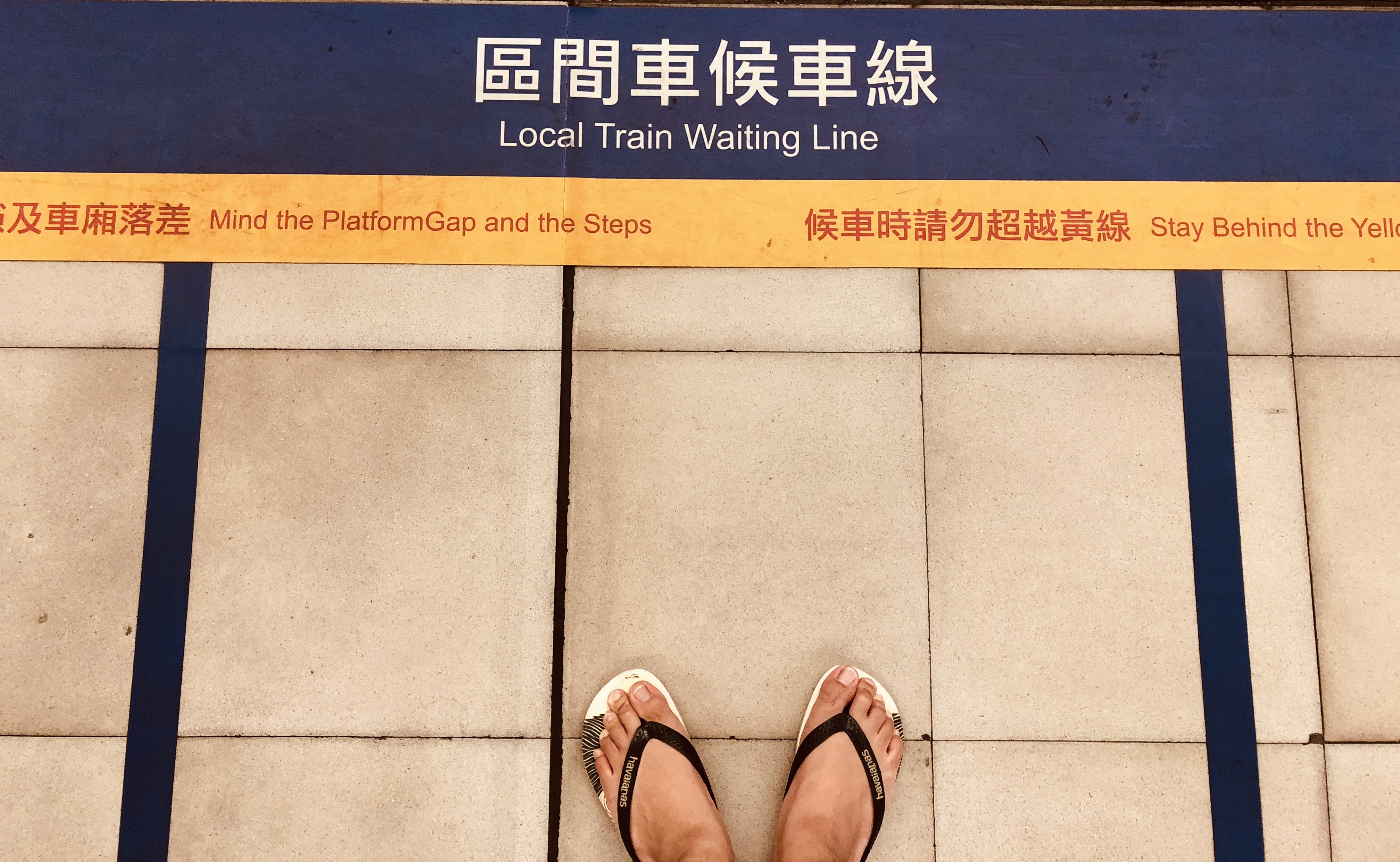 person facing local train waiting line signage
