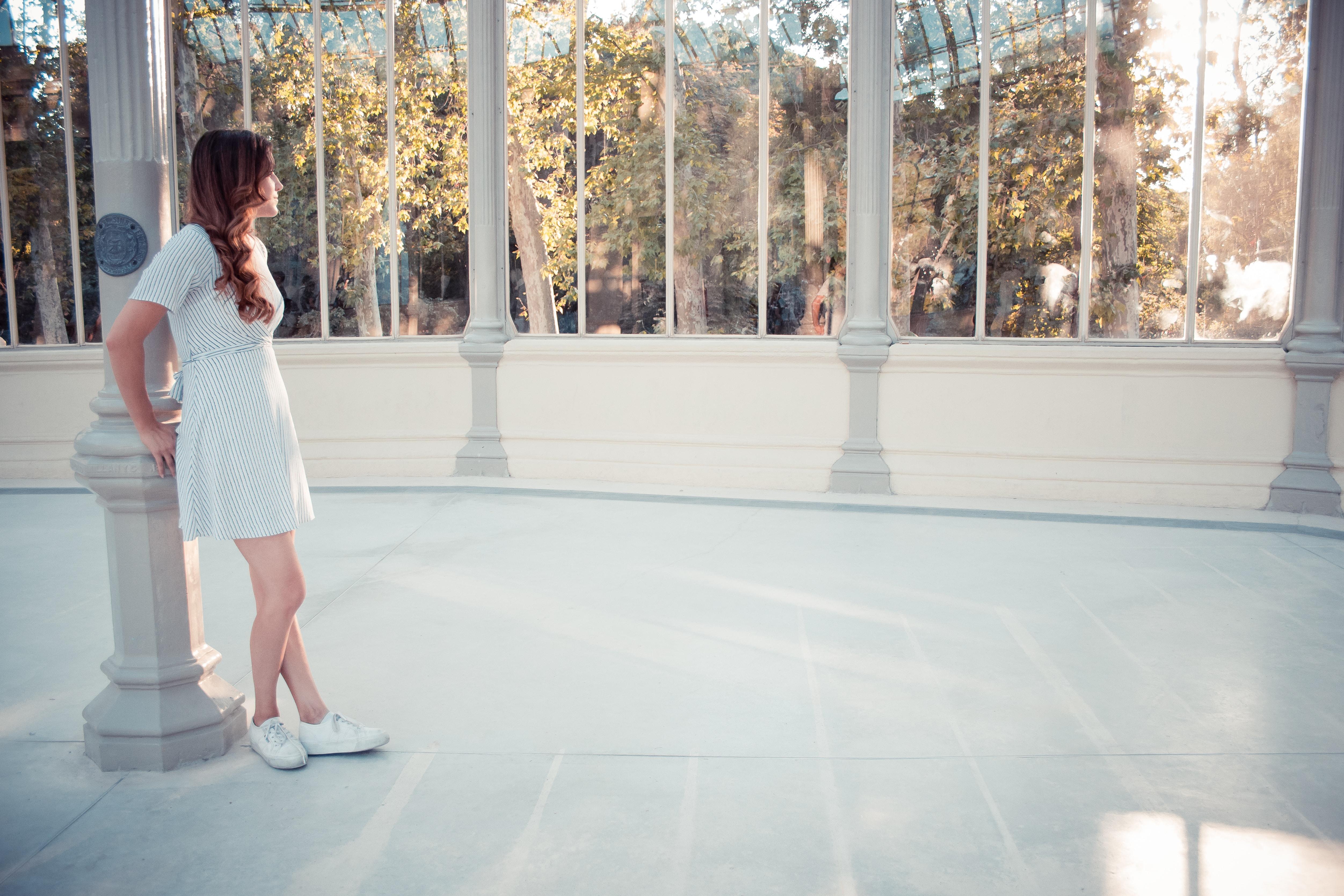 woman leaning on white concrete pillar