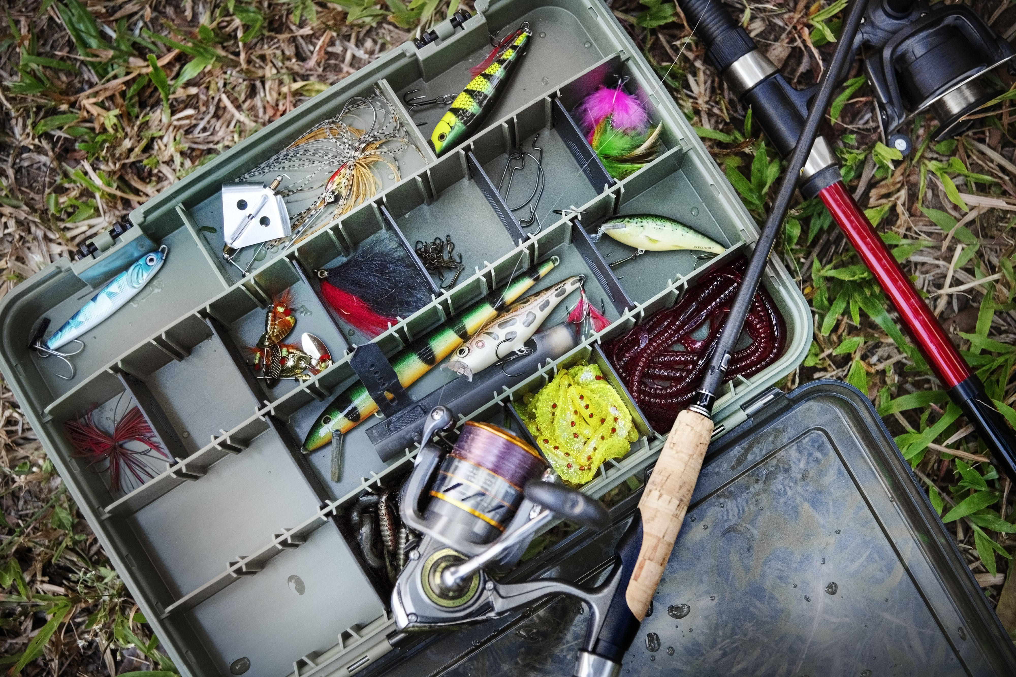 brown and black fishing rod and fishing reel on assorted fish lure lot inside plastic case