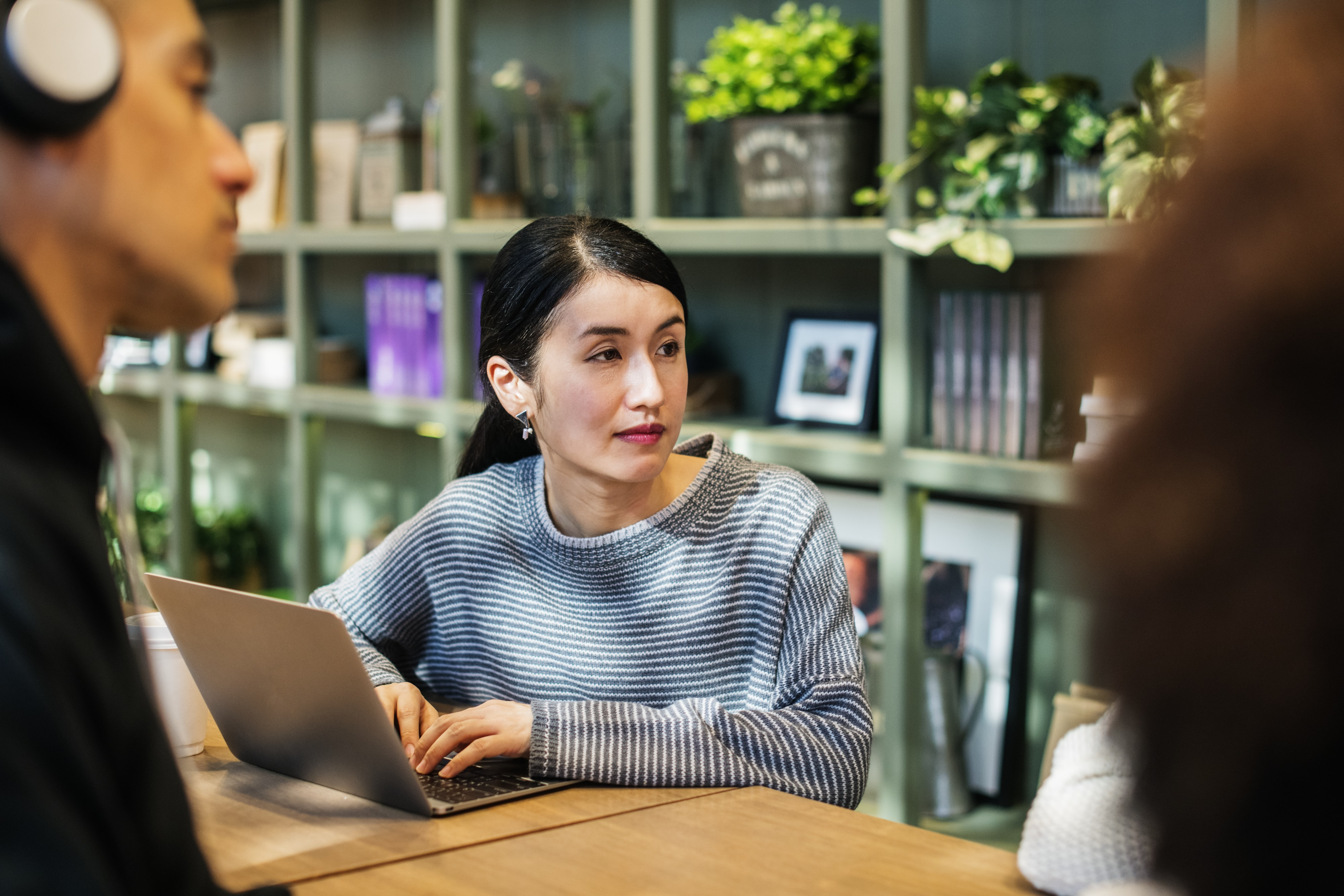 woman sitting in table using laptop while looking to her left