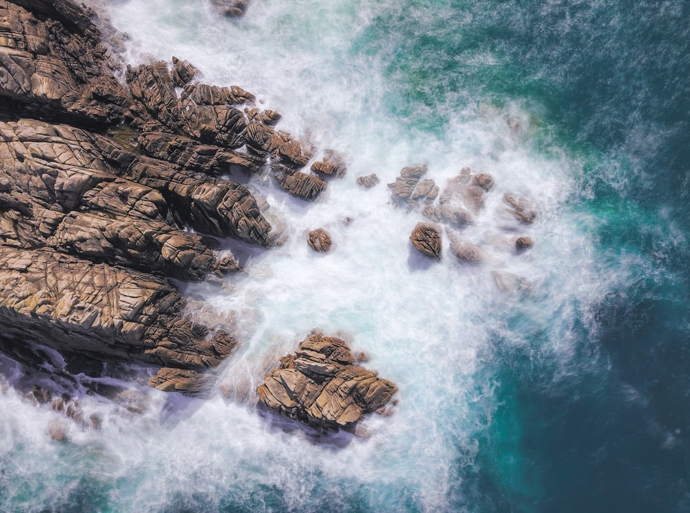 brown rock formation at the sea