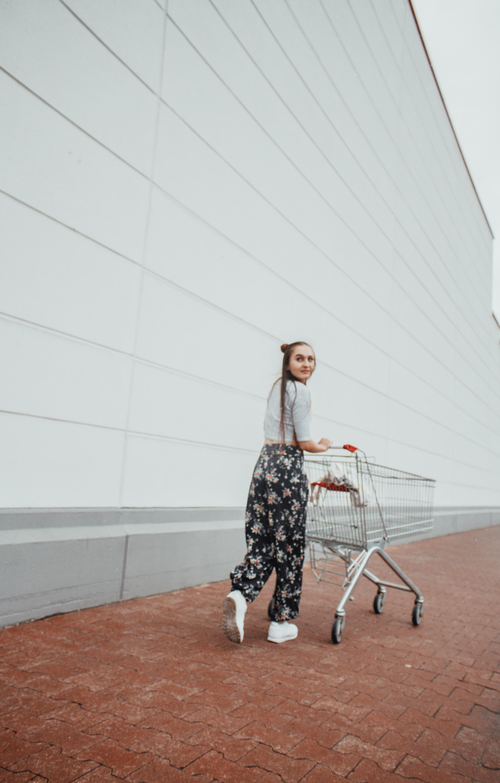 woman standing pushing shopping cart