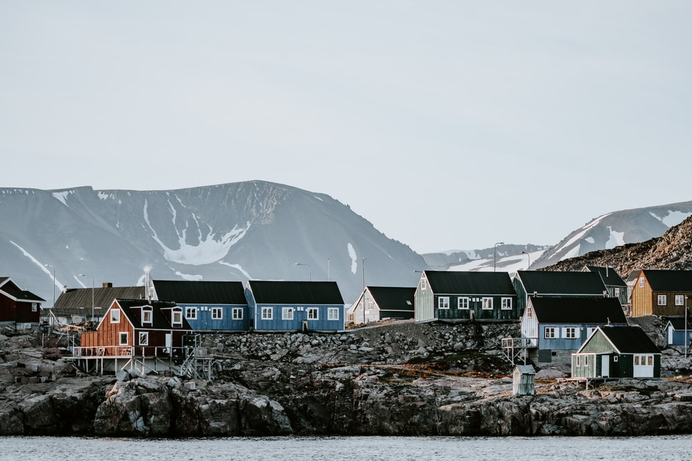 houses near mountain and body of water