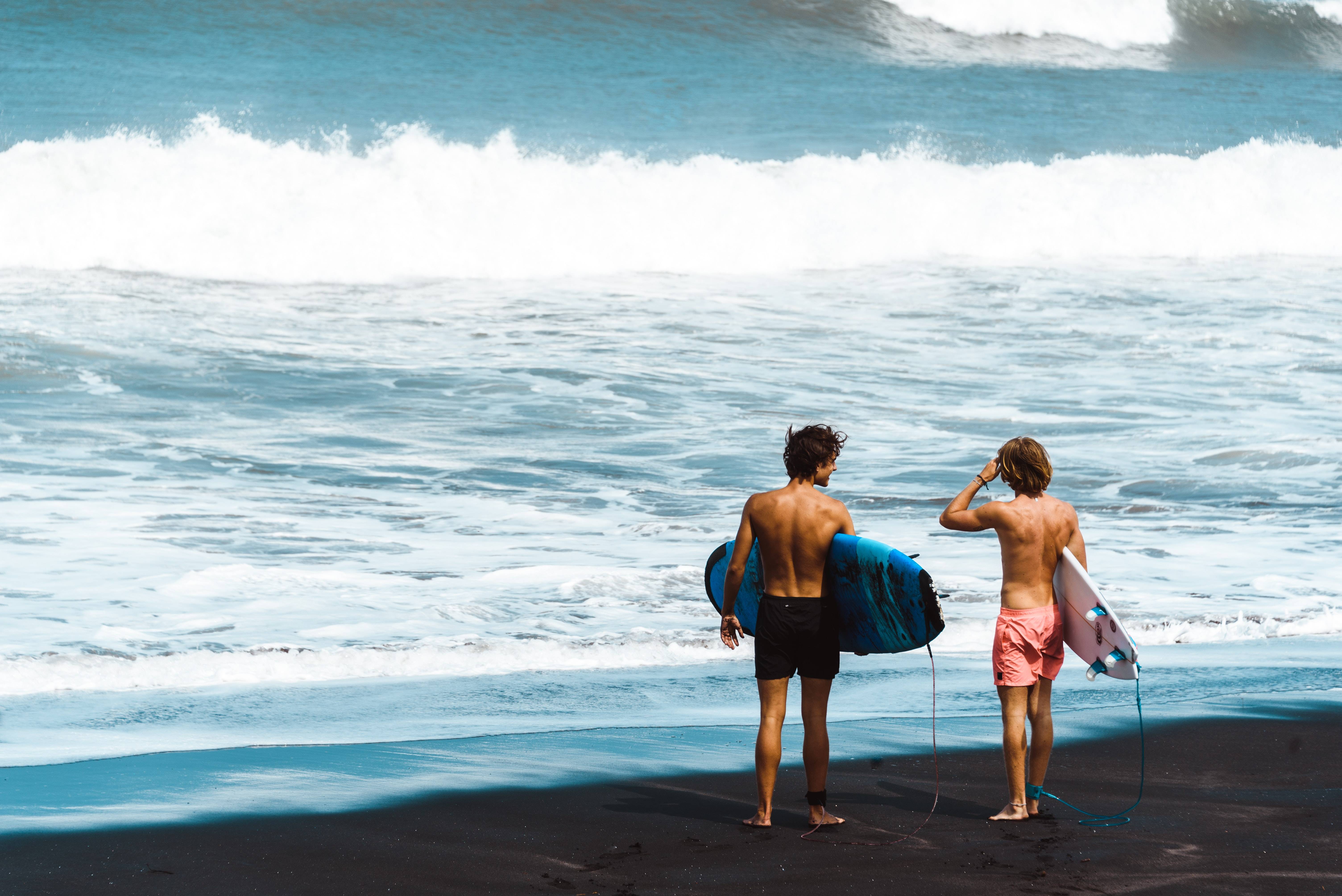 two men carrying surfboards on shoreline