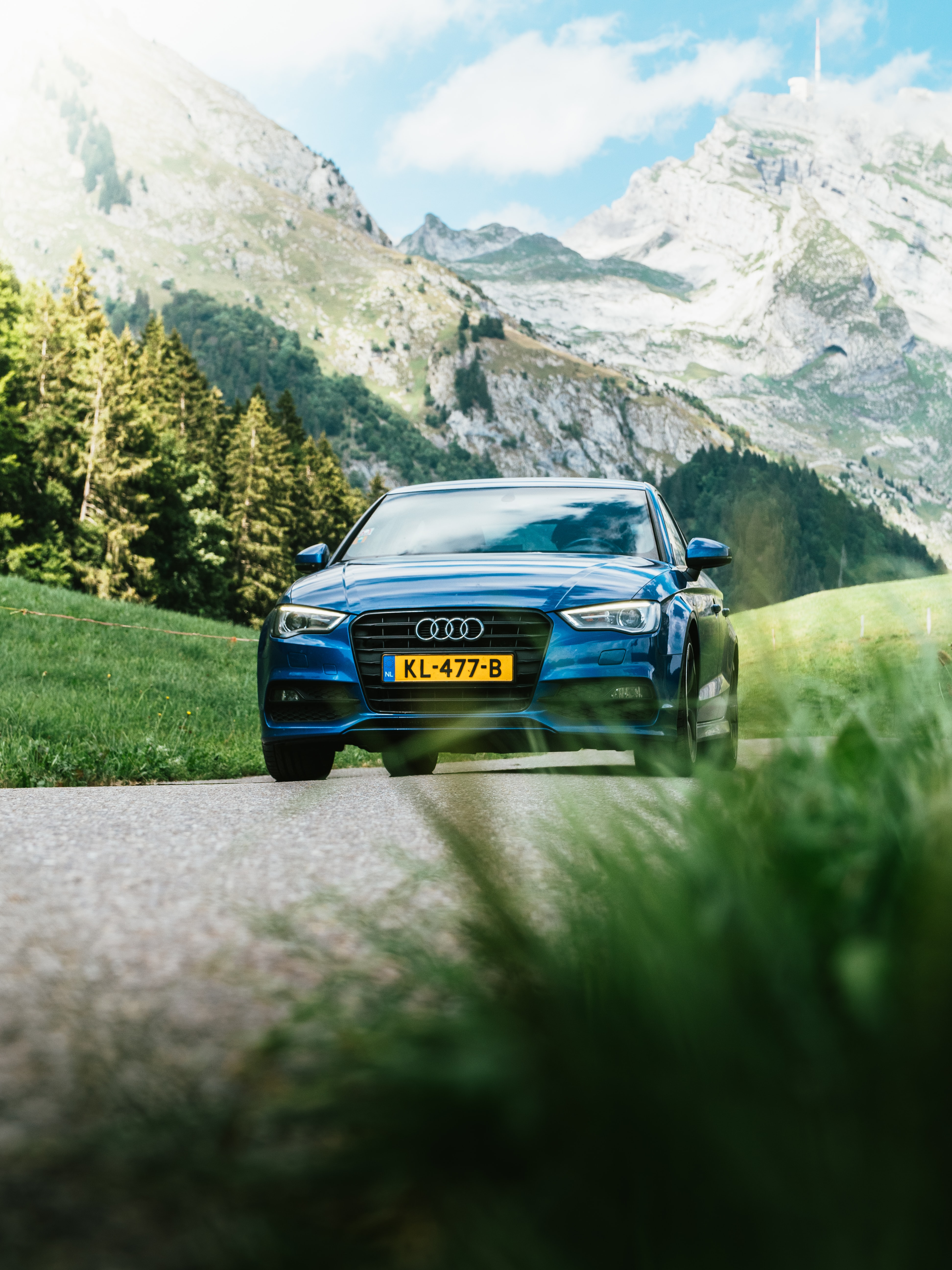 blue Audi vehicle traveling on road