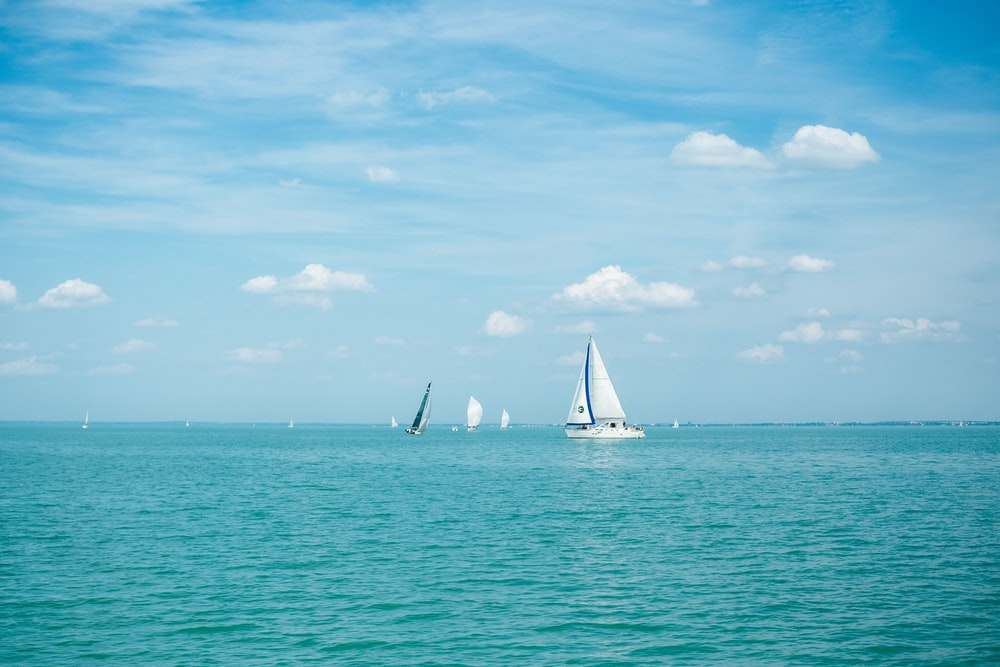 white sailing boat floating on body of water