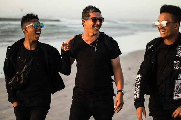 Three friends walking along the beach laugh together