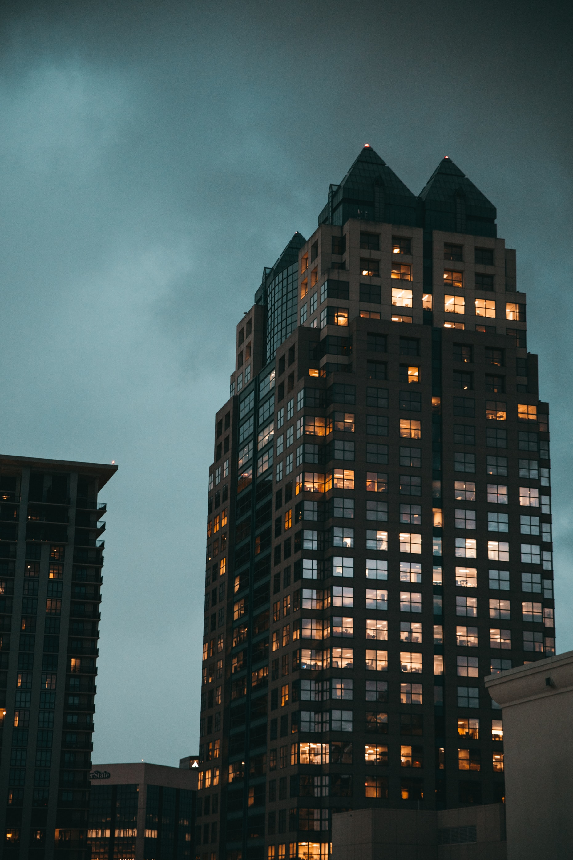 black glass-panel building under dark clouds