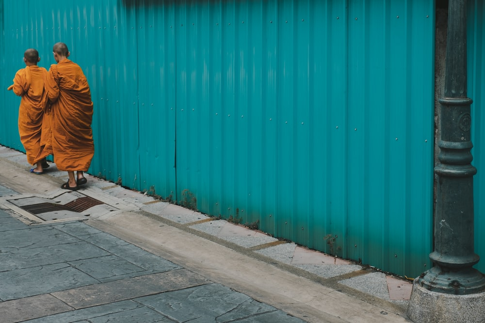 two monks walking beside blue painted galvanized wall