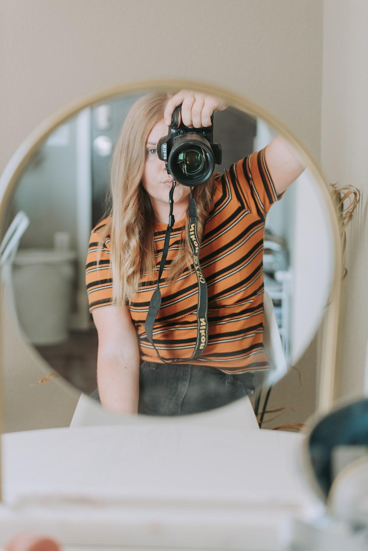 woman taking photo using black camera