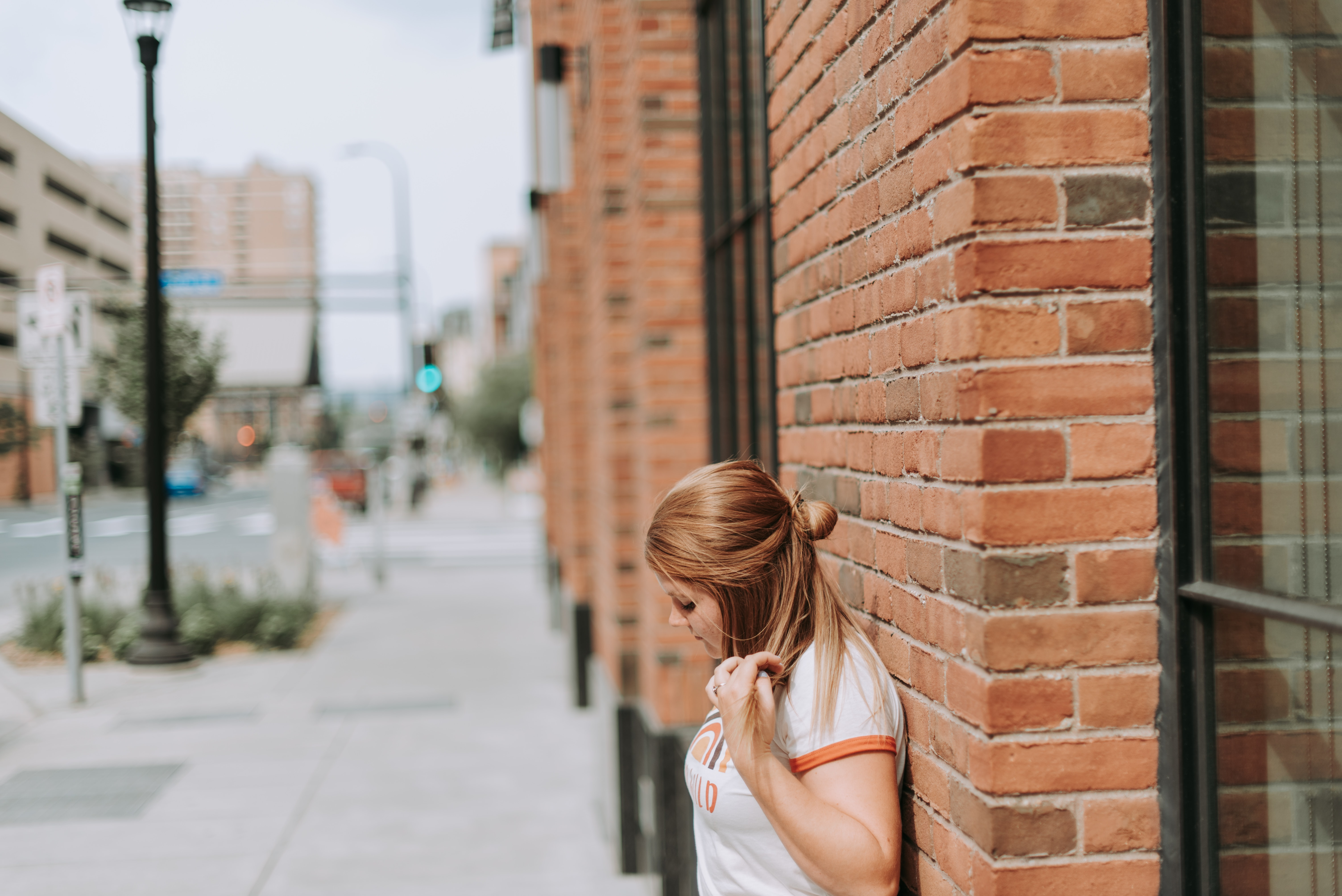 woman leaning on brown brick wall at daytime