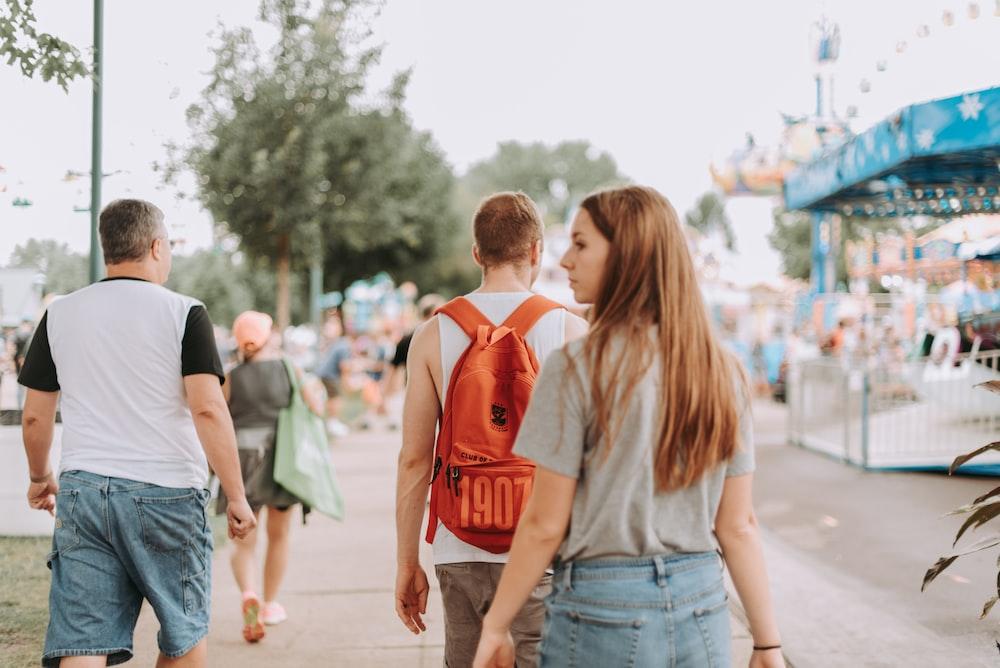 woman walking near two men in pathway during daytime