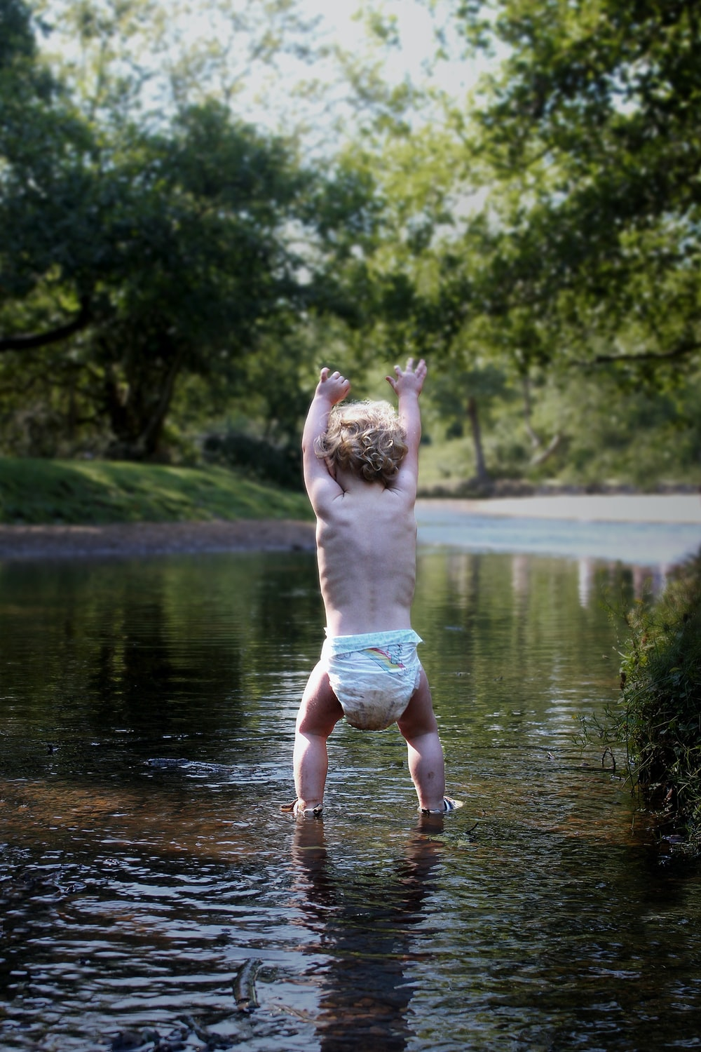 toddler standing on river