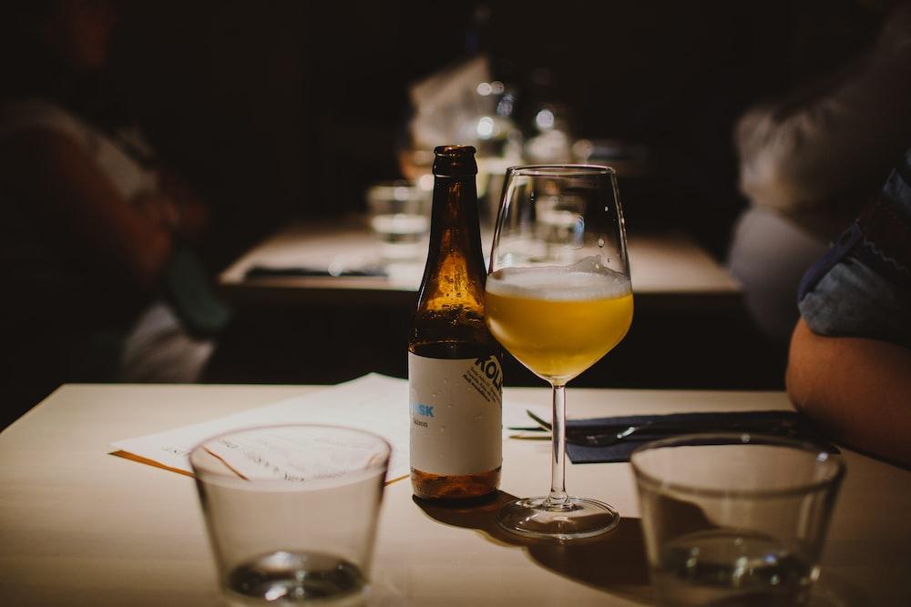beer bottle beside wine glass on table