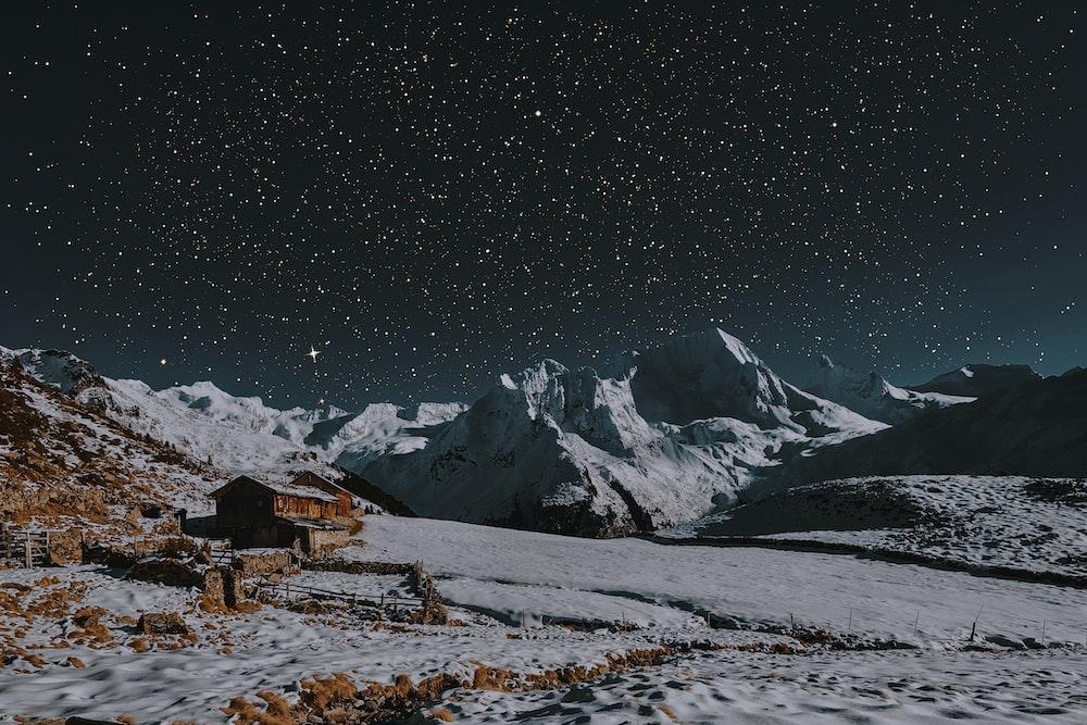 snow covered mountains under dark sky