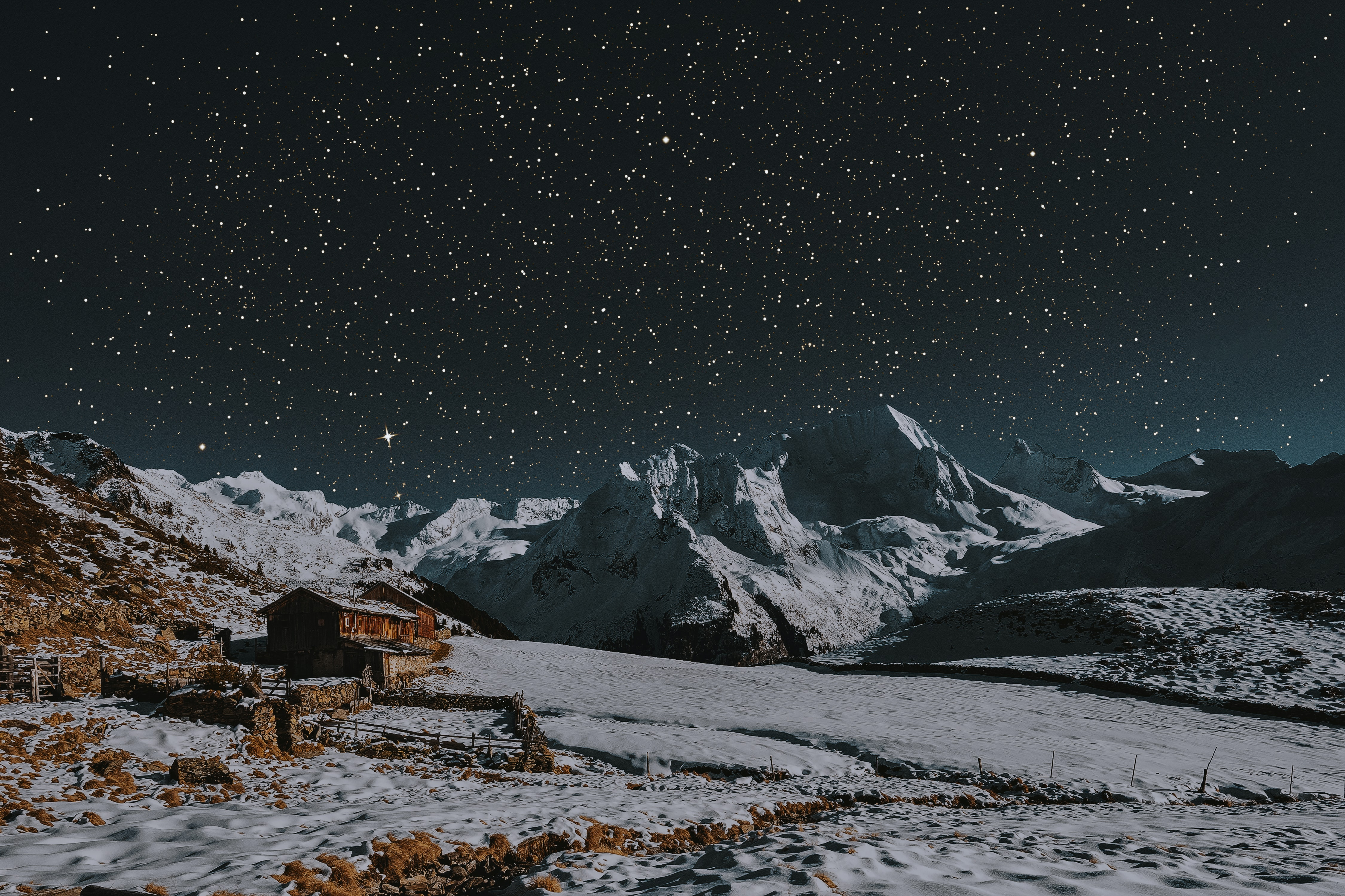 snow covered mountains under dark sky